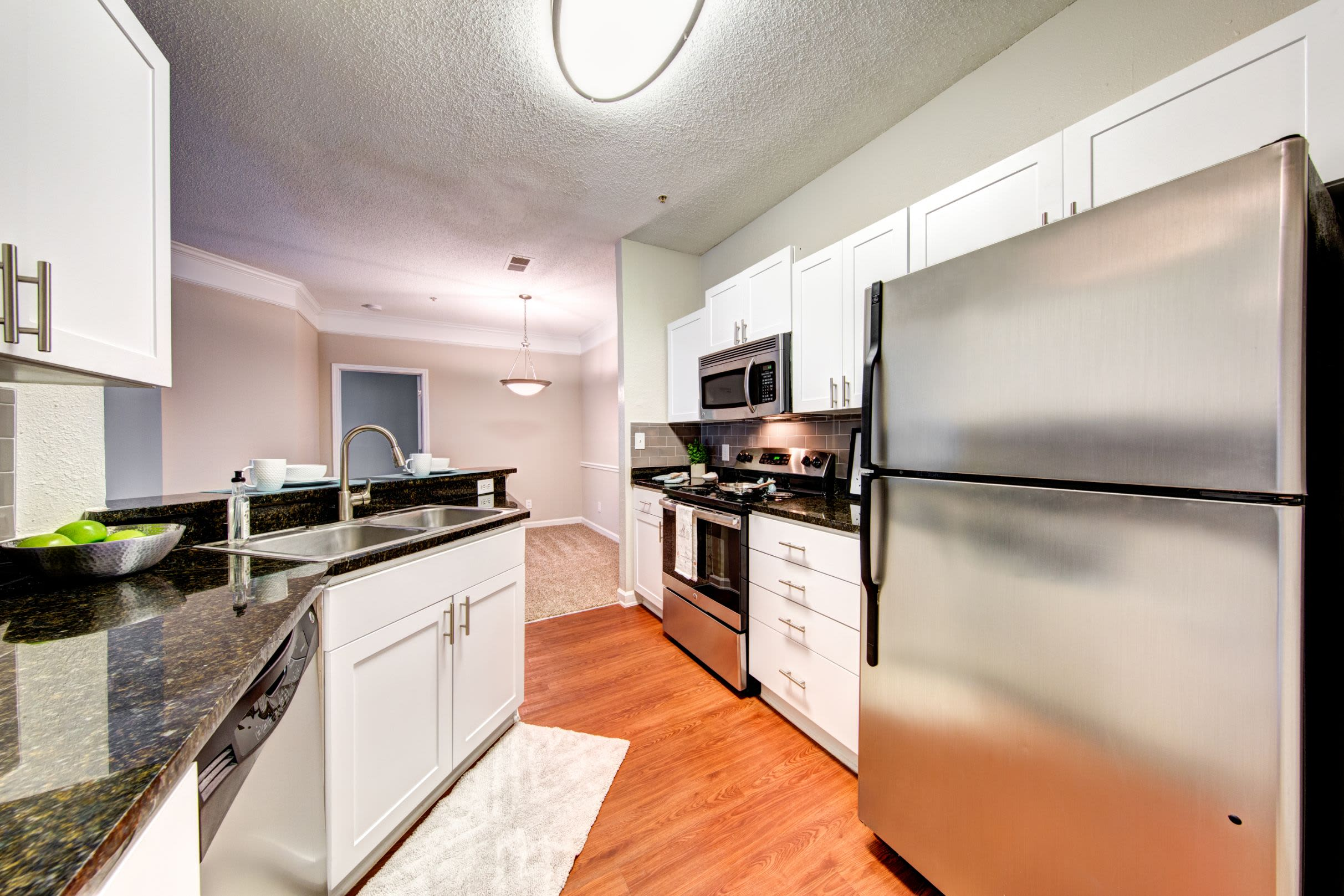 Bright kitchen with a large stainless steel fridge at Marquis on Edwards Mill in Raleigh, North Carolina