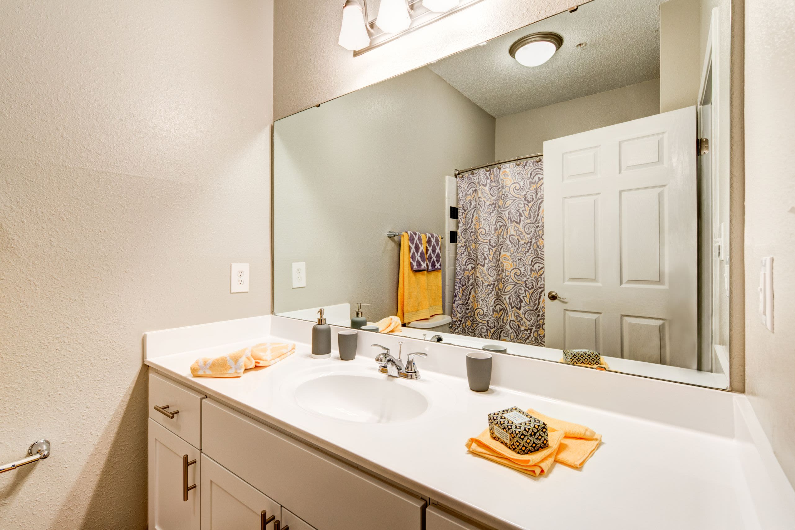 Bathroom with white cabinets and a large mirror at Marquis on Edwards Mill in Raleigh, North Carolina