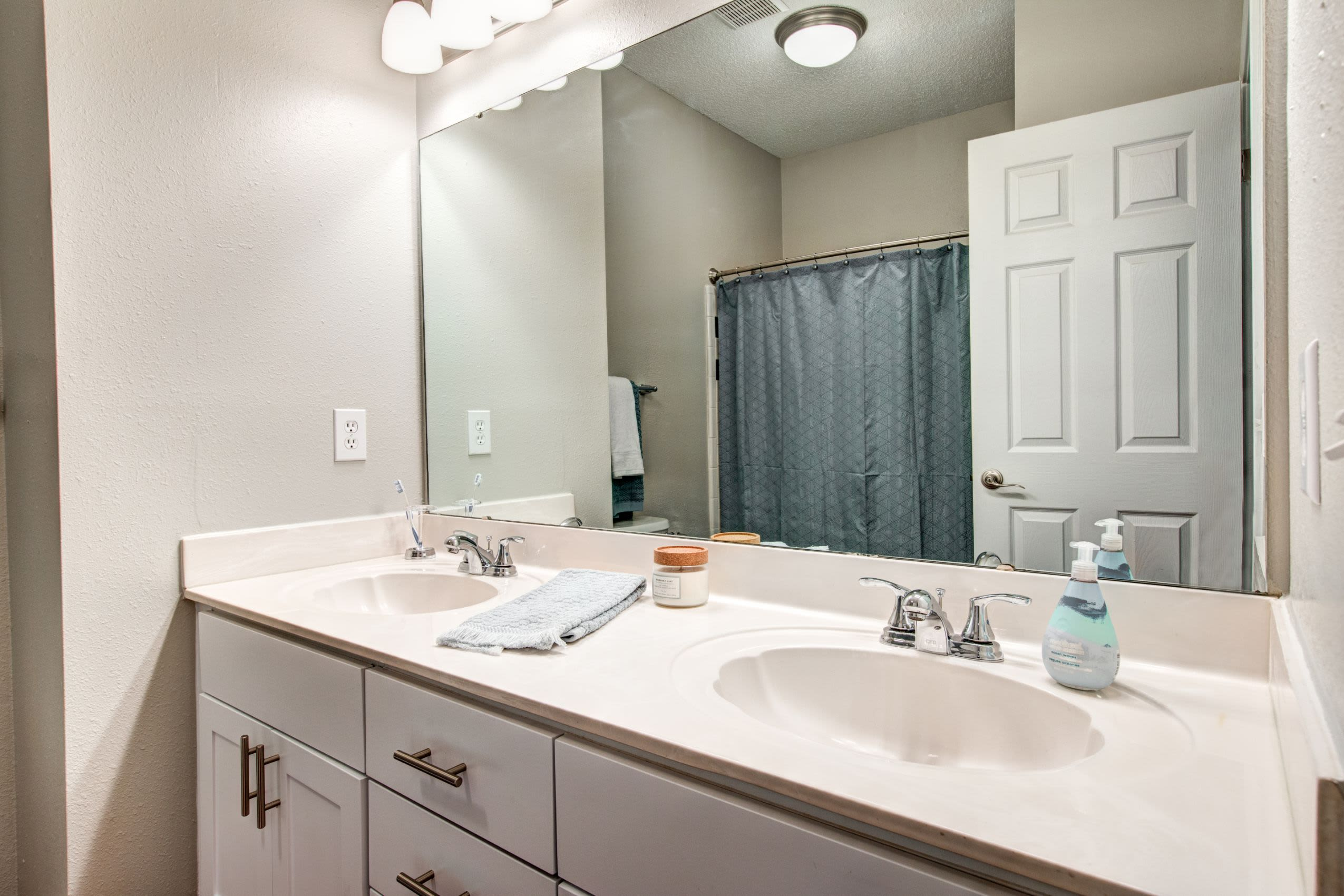 Bathroom with white counters and double sinks at Marquis on Edwards Mill in Raleigh, North Carolina