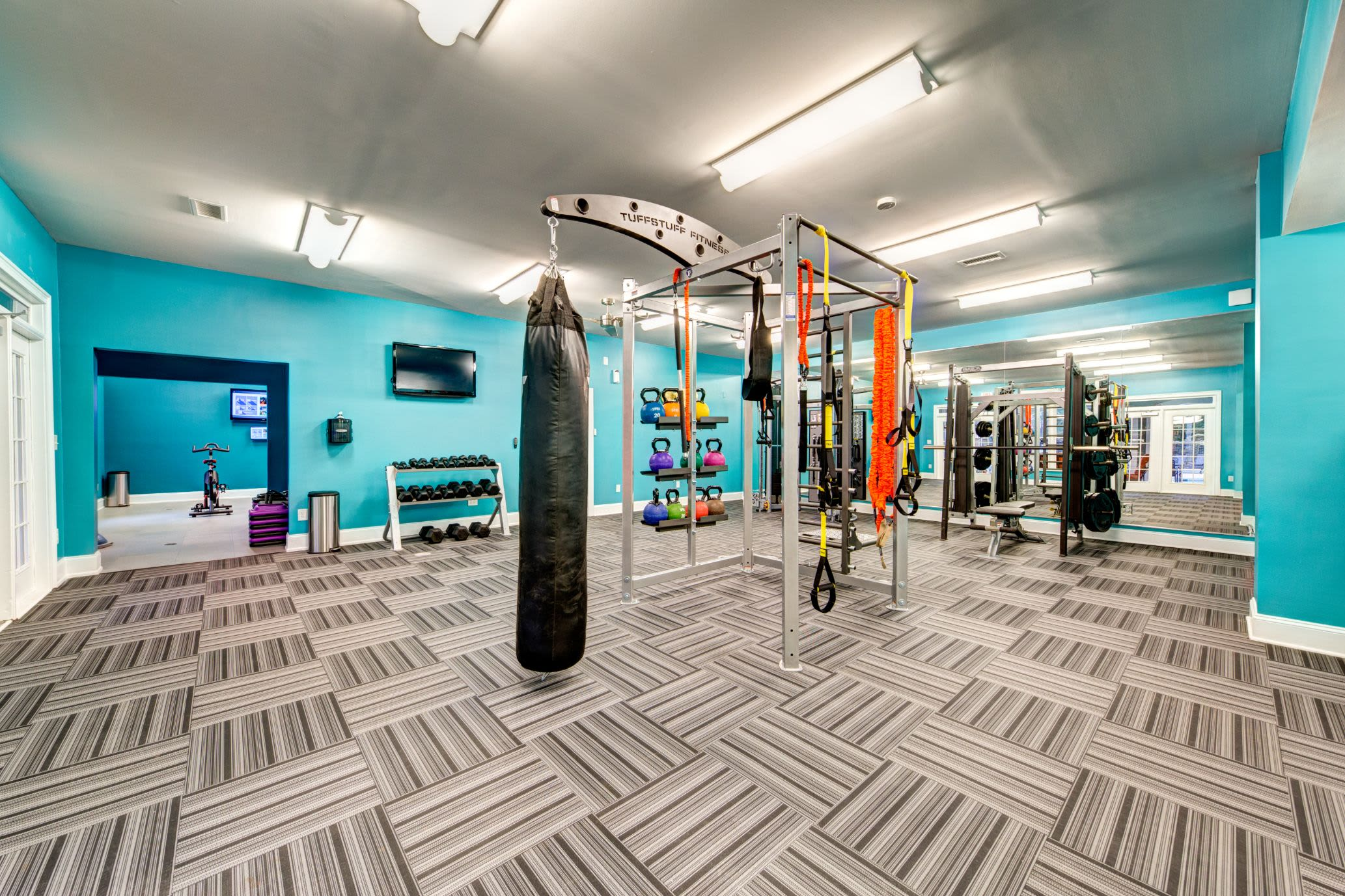 Free weights, TRX bands, and a punching bag in fitness center at Marquis on Edwards Mill in Raleigh, North Carolina