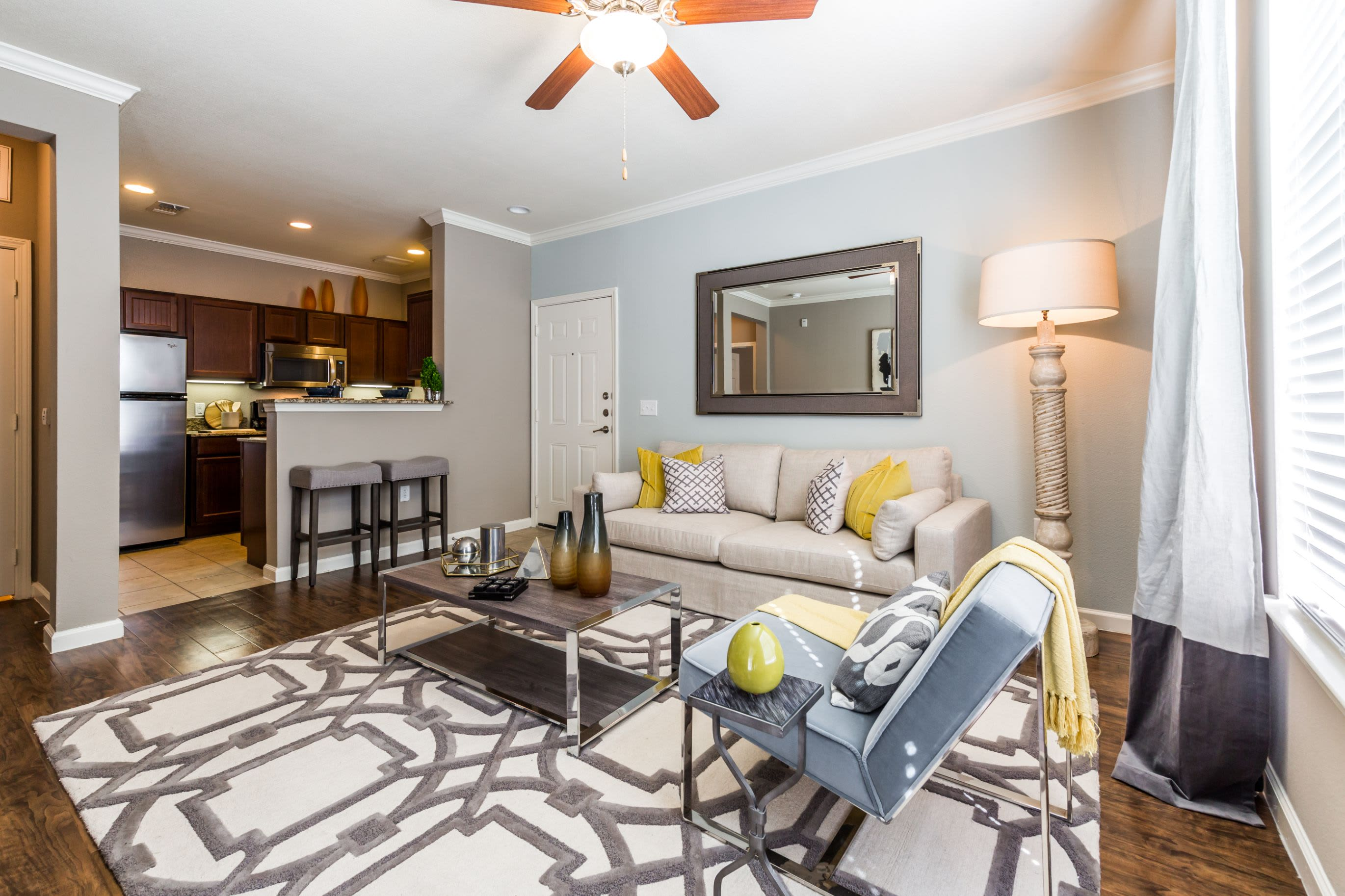 Open living room with a large rug and ceiling fan at Marquis at Crown Ridge in San Antonio, Texas