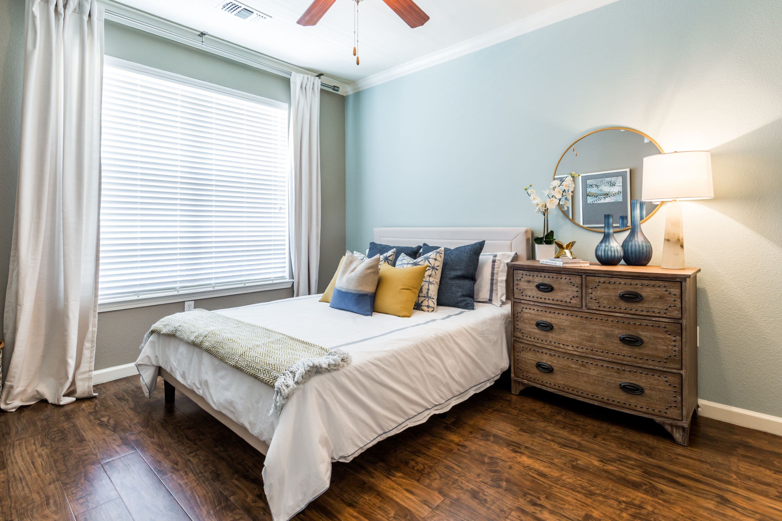 Bright bedroom with a large window at Marquis at Crown Ridge in San Antonio, Texas
