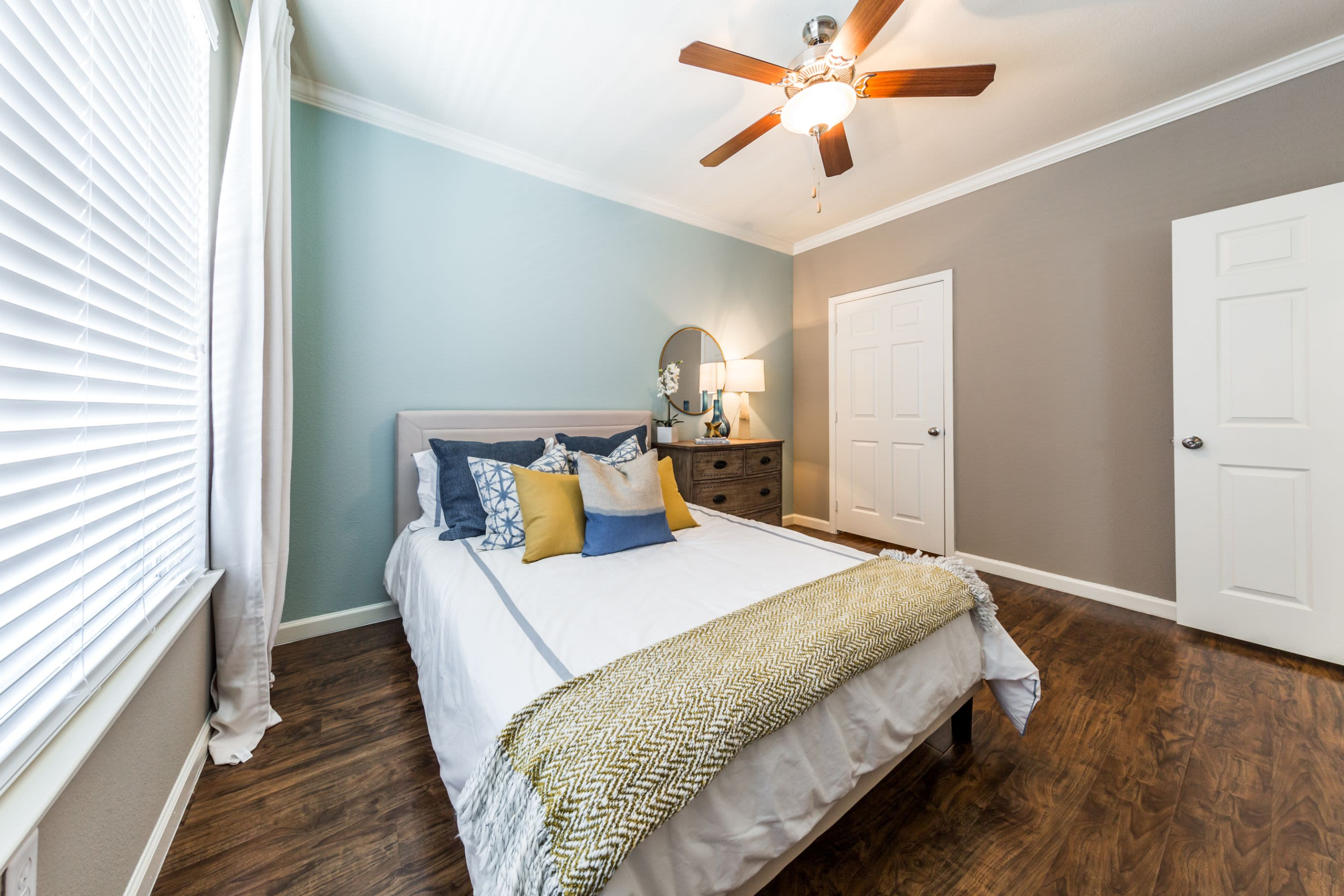 Bright bedroom with wood floors and a ceiling fan at Marquis at Crown Ridge in San Antonio, Texas