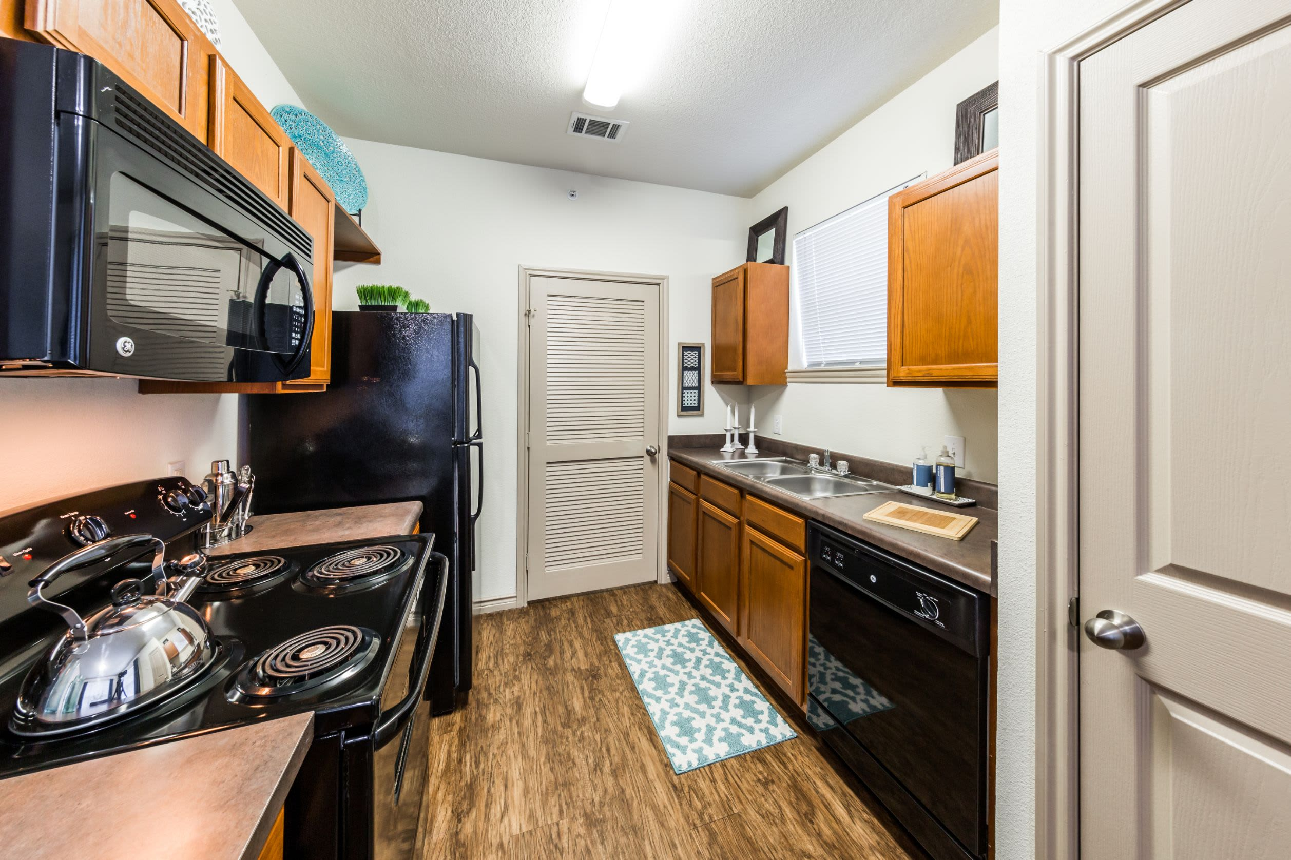 Bright kitchen with wood floors and black appliances at The Marquis at Brushy Creek in Austin, Texas