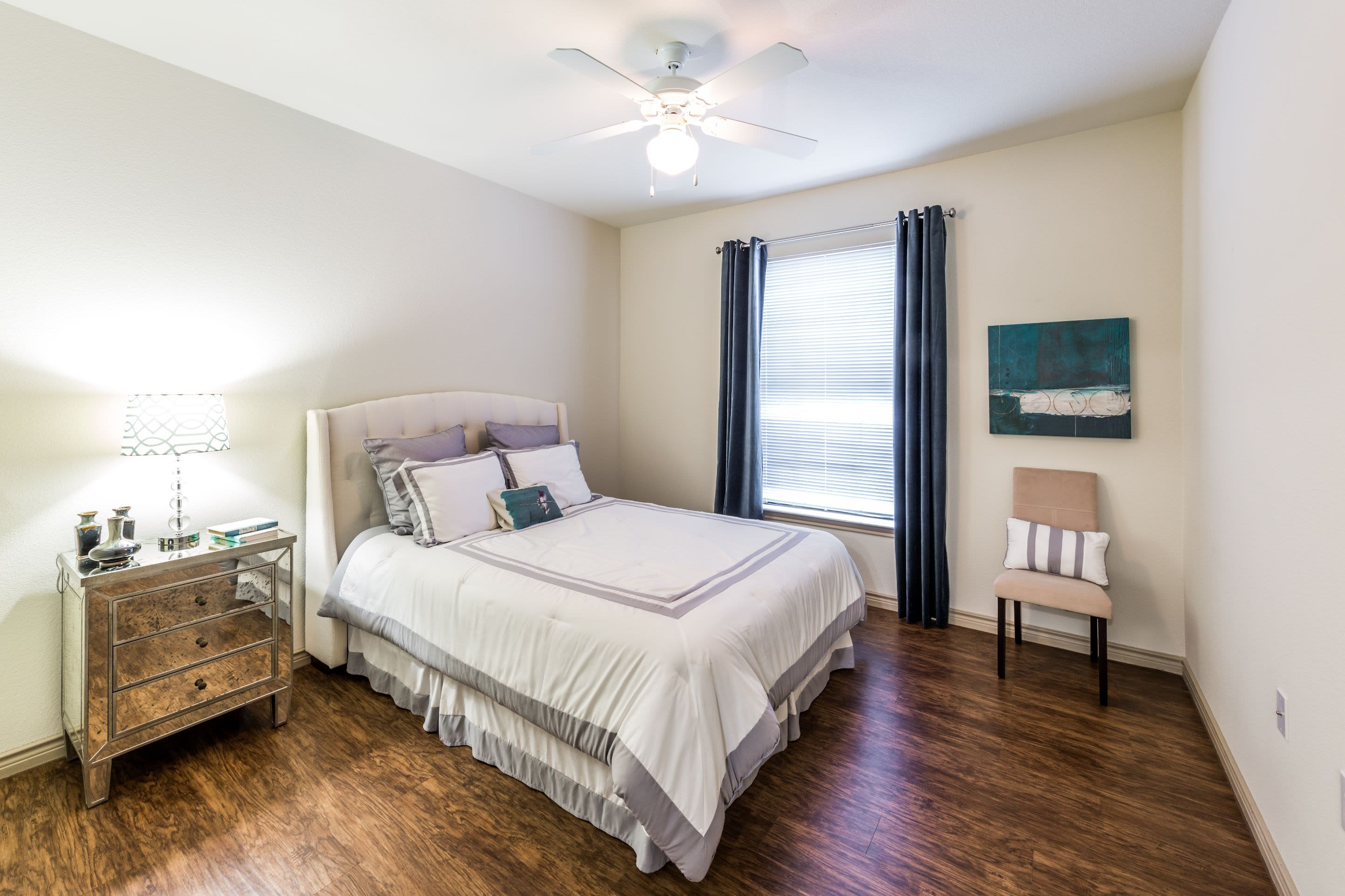 Bright and cheerful bedroom with wood flooring at The Marquis at Brushy Creek in Austin, Texas
