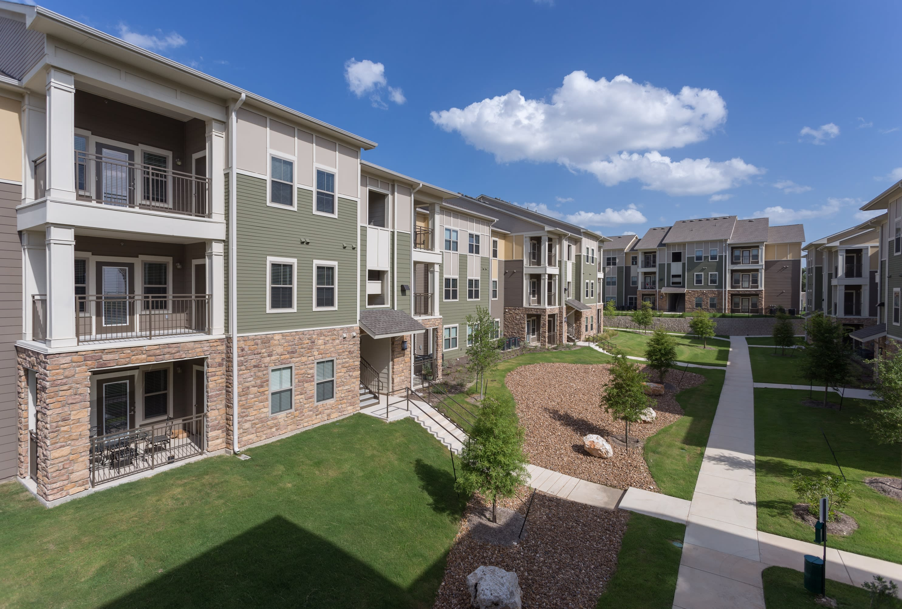 Buildings and walkways with landscaping at Encore 281 in San Antonio, Texas