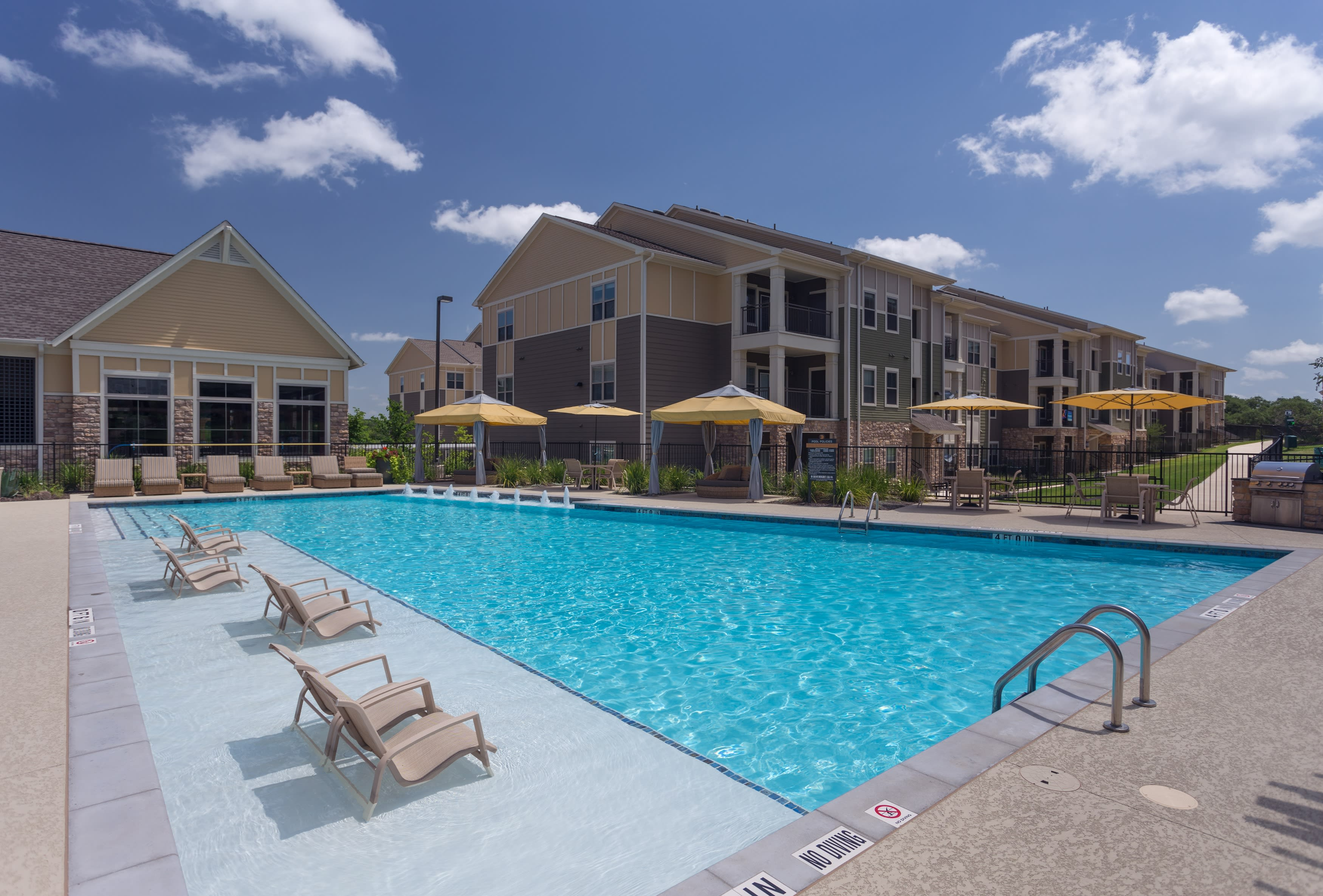 Sparkling blue pool with lounge chairs at Encore 281 in San Antonio, Texas