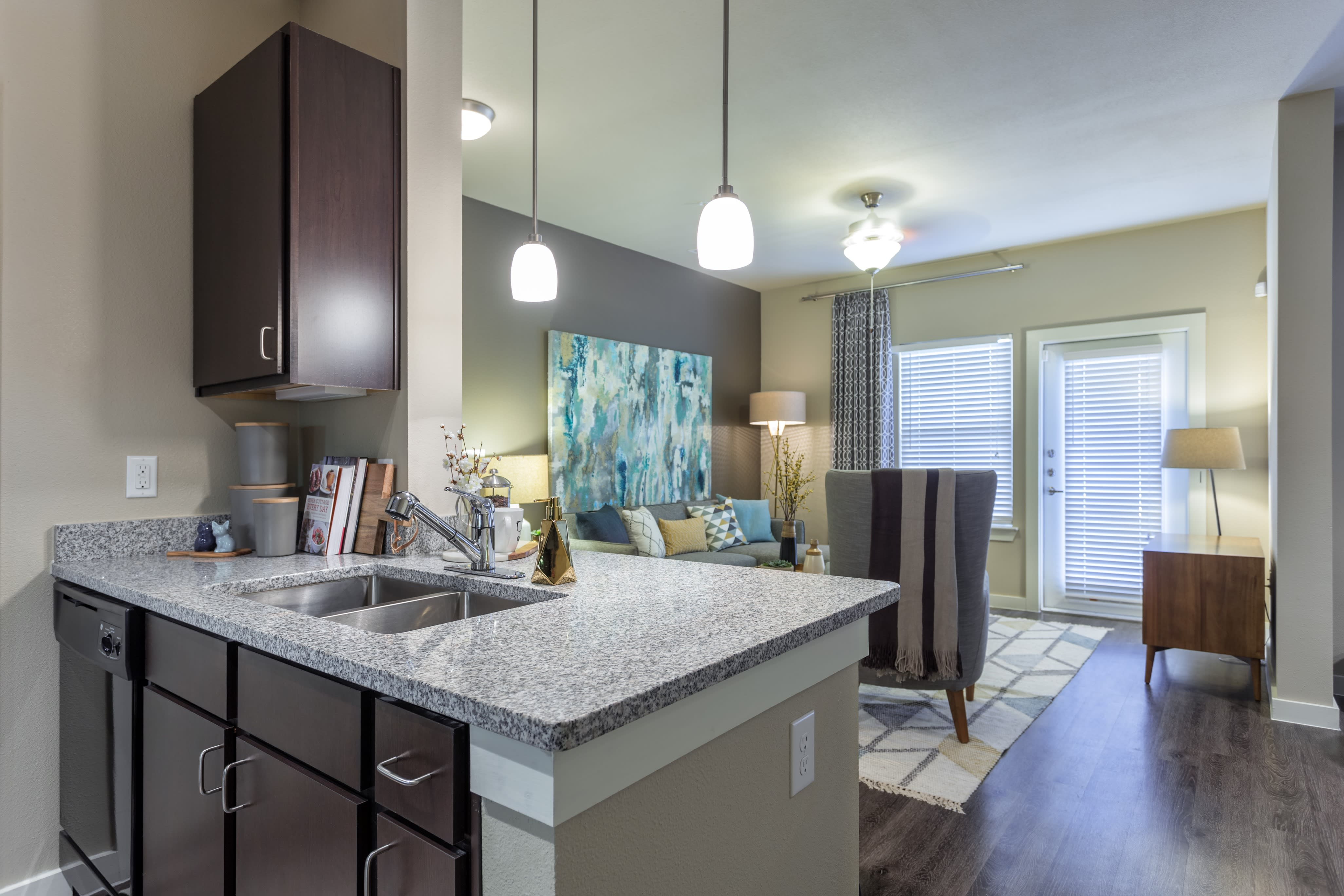 Modern kitchen with a bar overlooking the living room in an apartment at Encore 281 in San Antonio, Texas