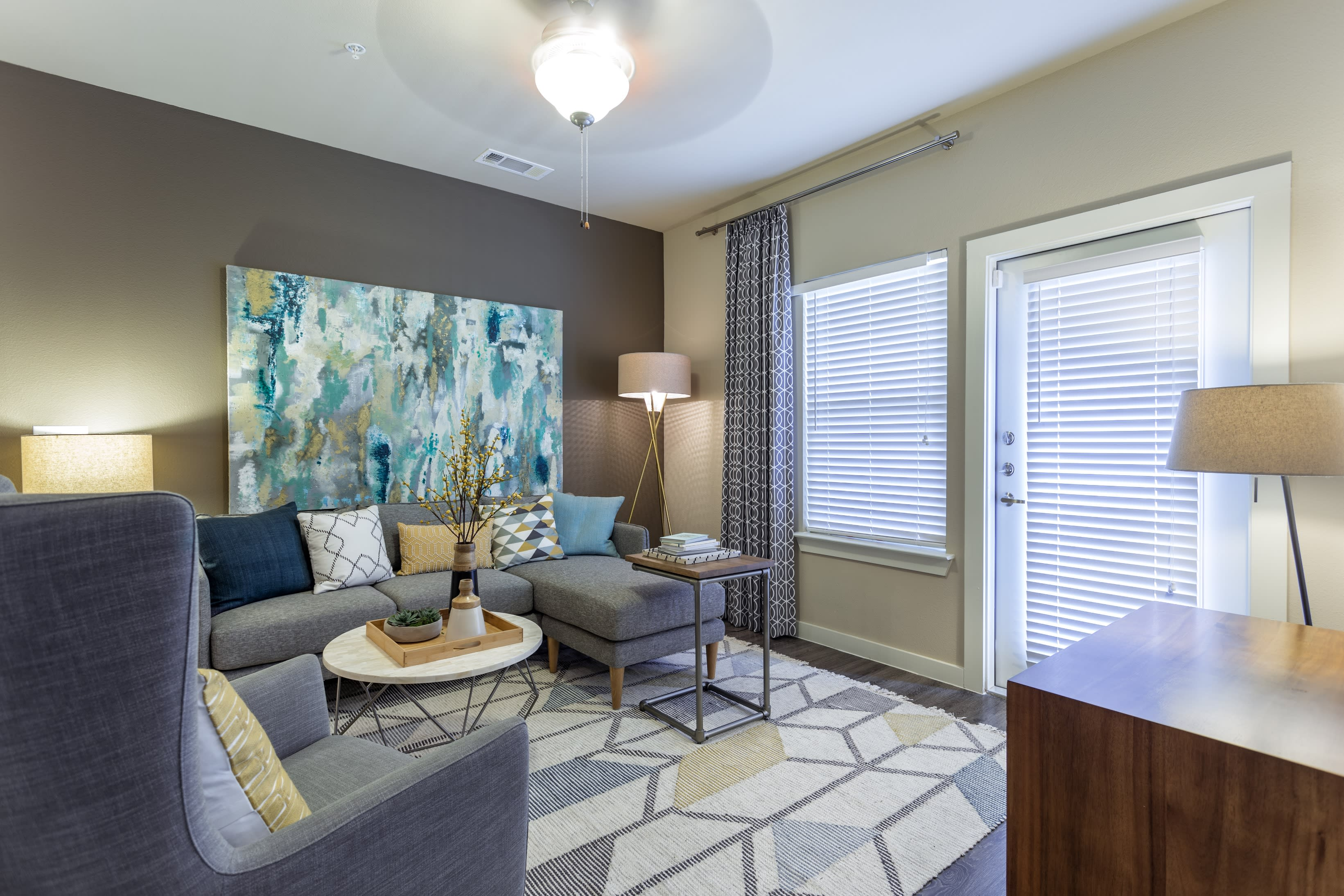 Spacious living room with large windows at Encore 281 in San Antonio, Texas