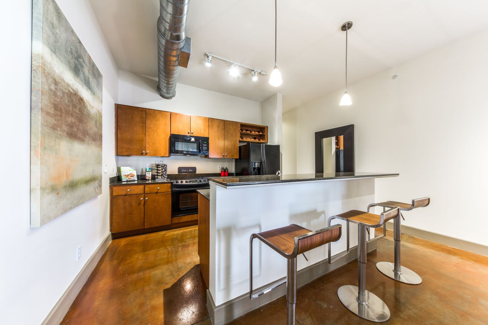 Kitchen with a breakfast bar at Marquis Lofts on Sabine in Houston, Texas