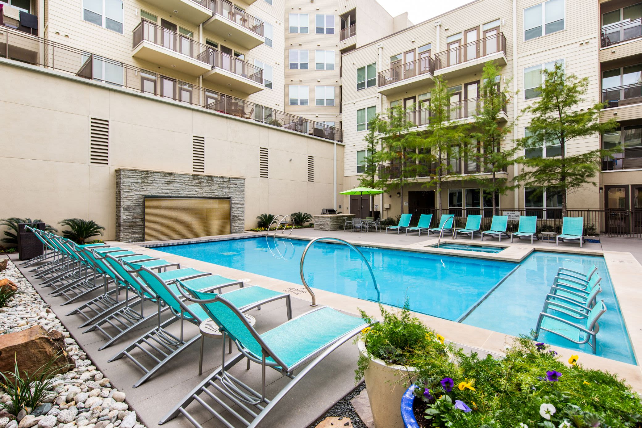 Sparkling swimming pool with lounge chairs on deck at The Marq on West 7th in Fort Worth, Texas