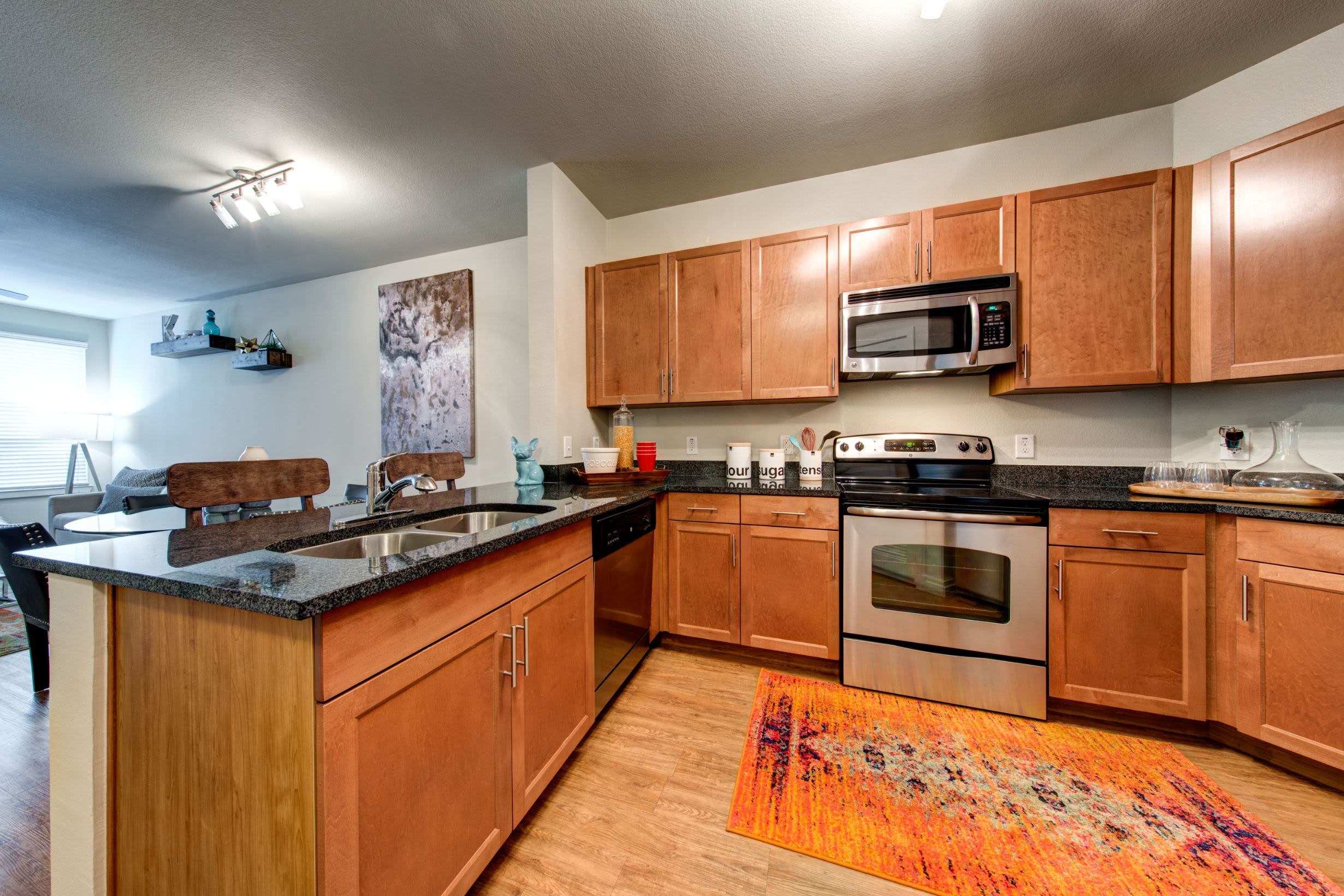 Kitchen with modern appliances and wood floors at The Marq on West 7th in Fort Worth, Texas
