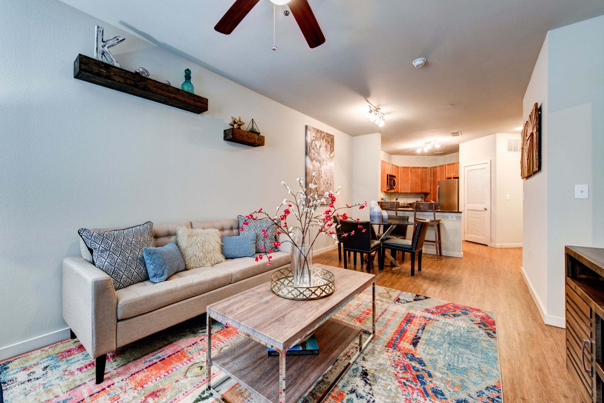 Open living area with wood floors and a large rug at The Marq on West 7th in Fort Worth, Texas