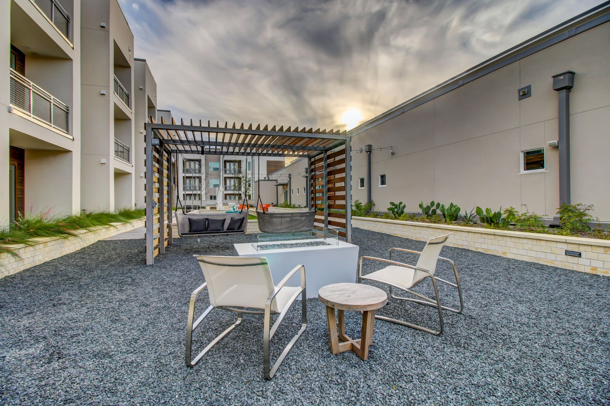 Gravel courtyard with a fire place and swinging chairs at Westerly 360 in Austin, Texas