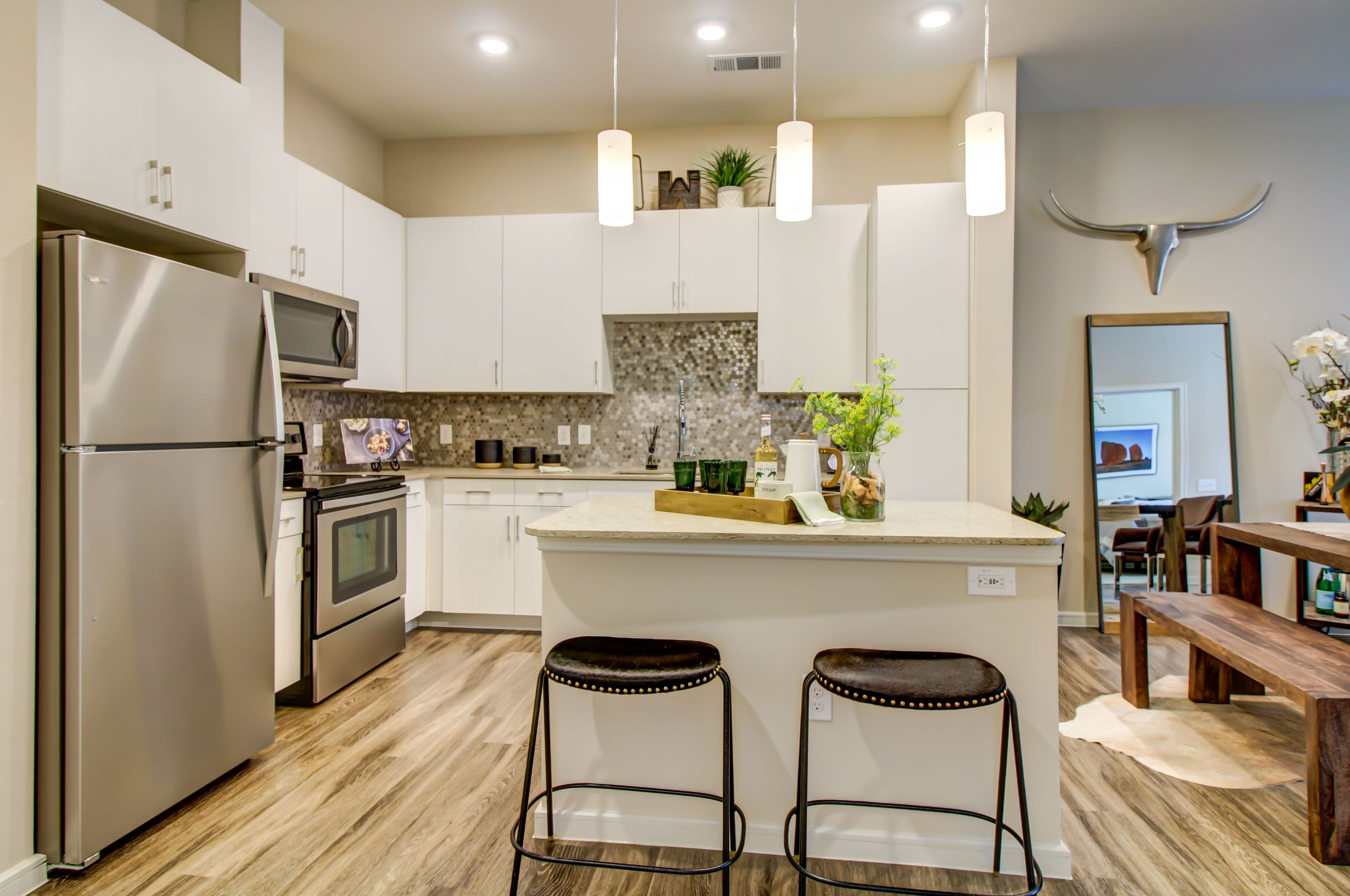 Modern kitchen with white cabinets and breakfast bar at Westerly 360 in Austin, Texas
