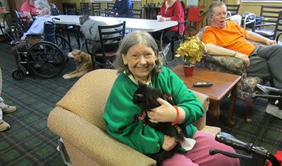 Smiling resident with cat at Avalon Assisted Living Community in Fitchburg, Wisconsin