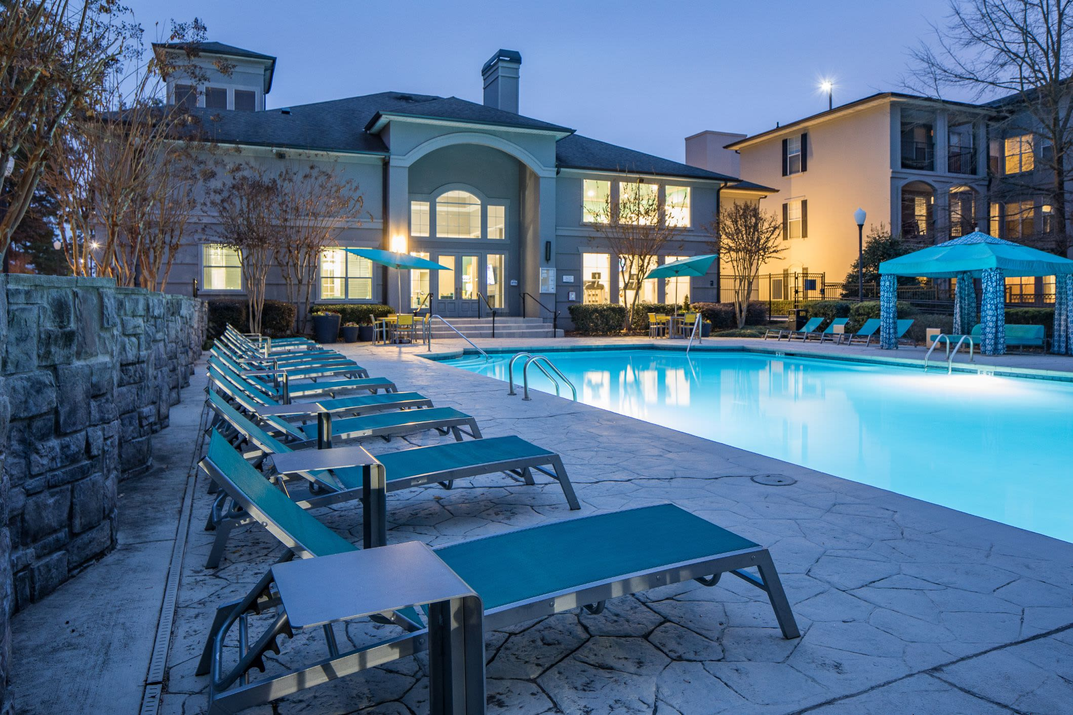 Swimming pool at dusk with the clubhouse behind it at Marq Perimeter in Atlanta, Georgia