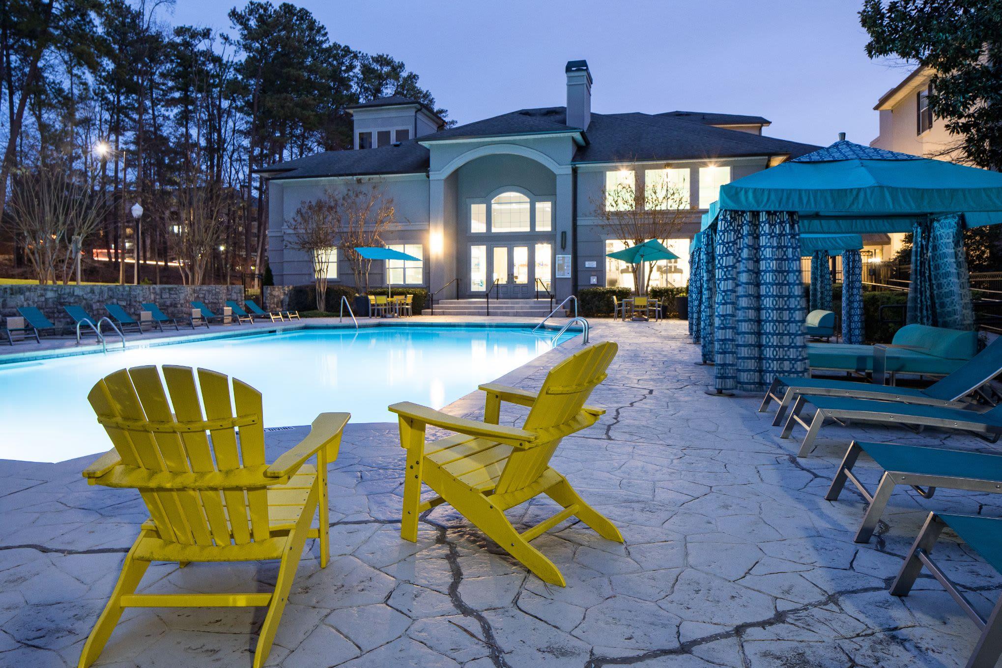 Swimming pool at dusk with Adirondack chairs on deck  at Marq Perimeter in Atlanta, Georgia