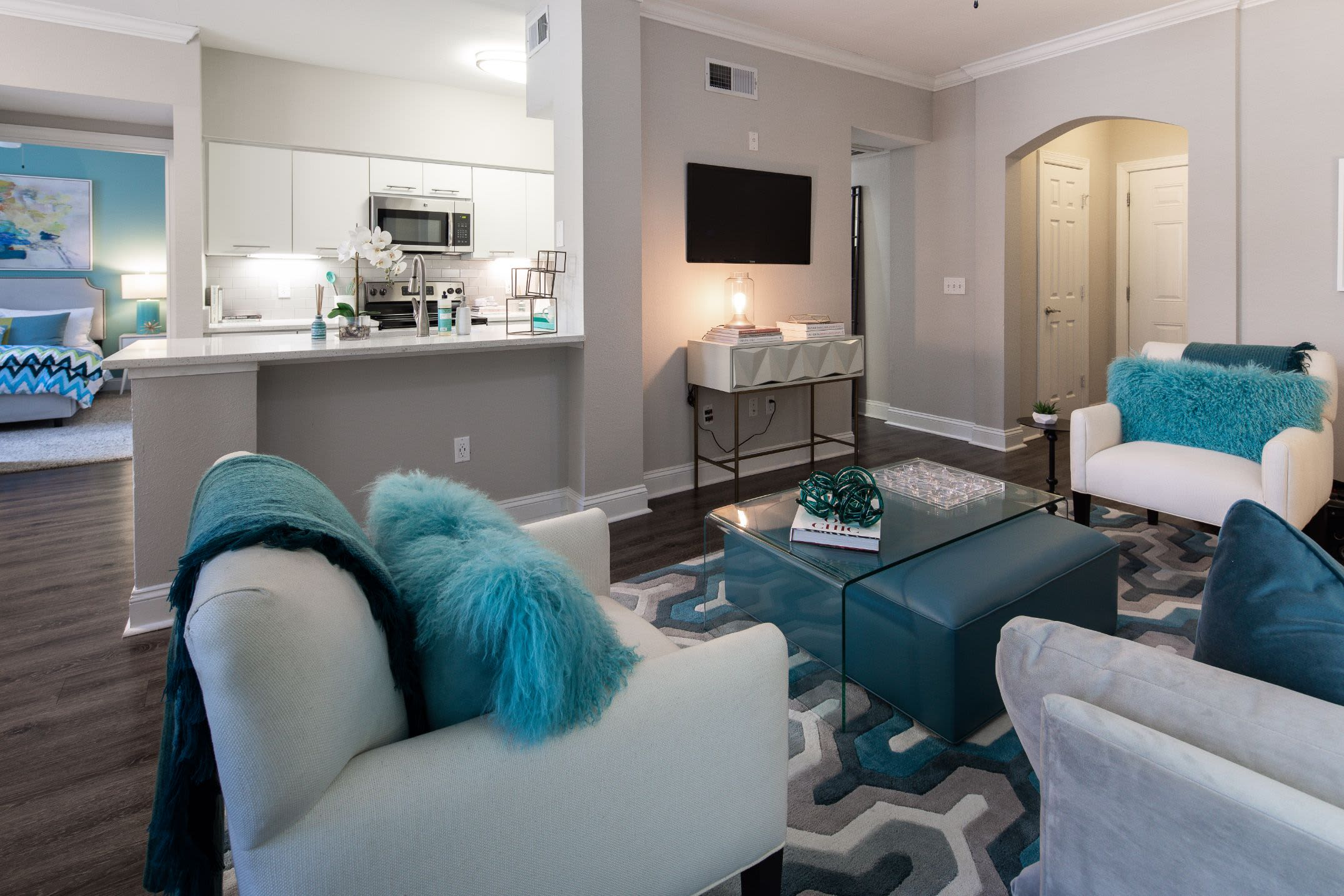 Open living area with kitchen behind it at Marq Perimeter in Atlanta, Georgia