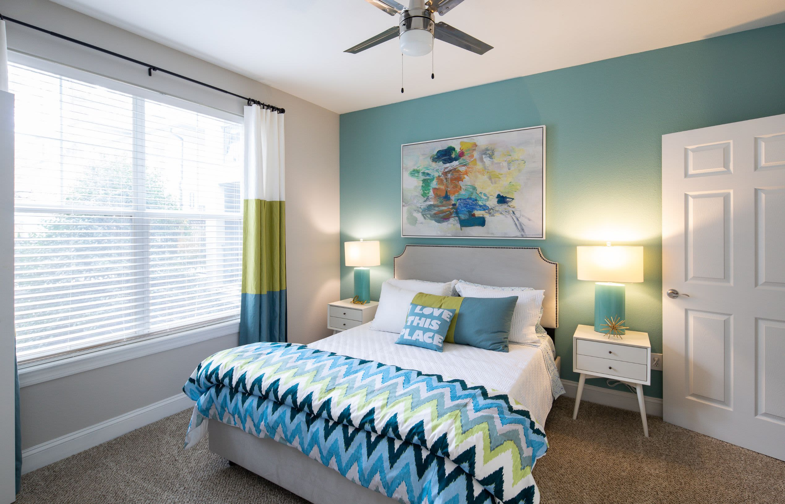 Spacious bedroom with large windows and a ceiling fan at Marq Perimeter in Atlanta, Georgia