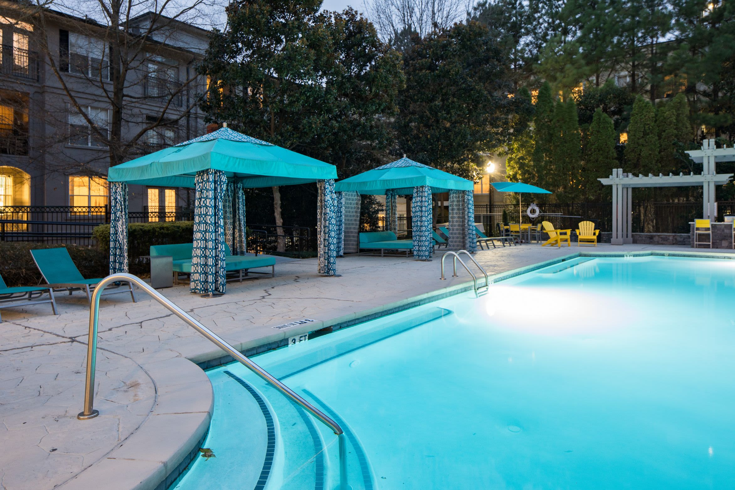 Swimming pool with covered lounge chairs on deck at Marq Perimeter in Atlanta, Georgia