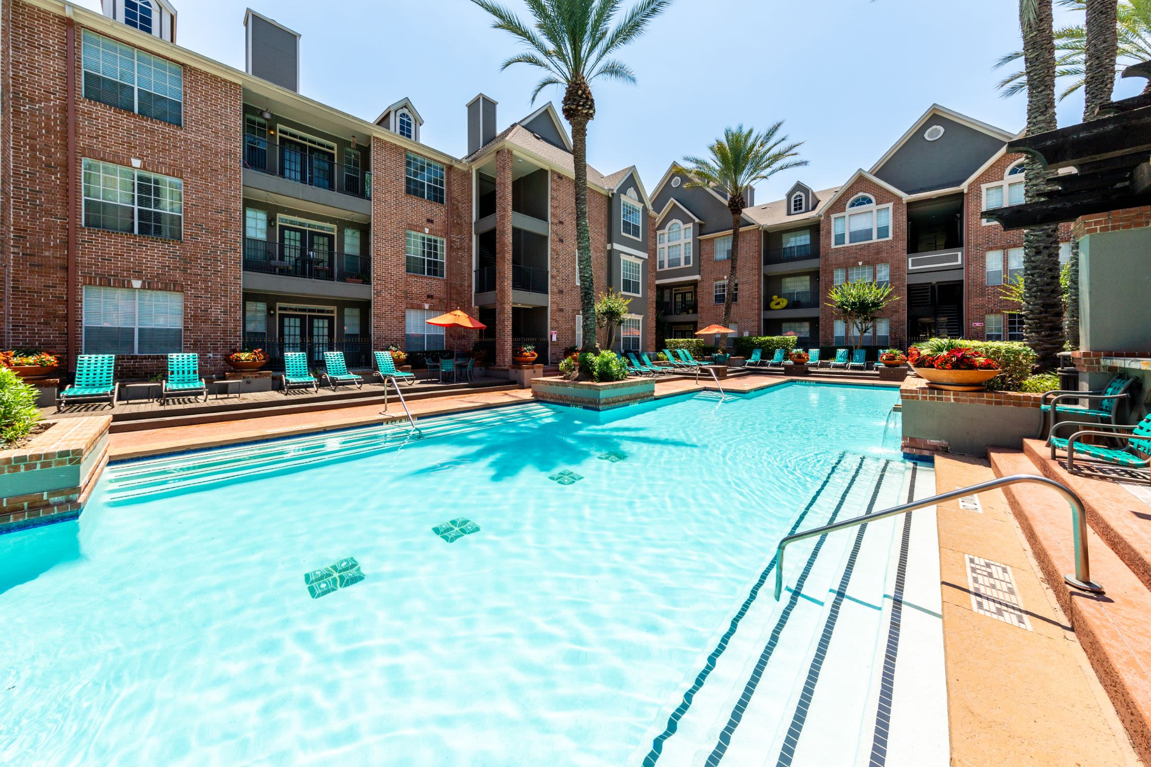 Sparkling pool with lounge chairs on deck at Marquis on Pin Oak in Houston, Texas