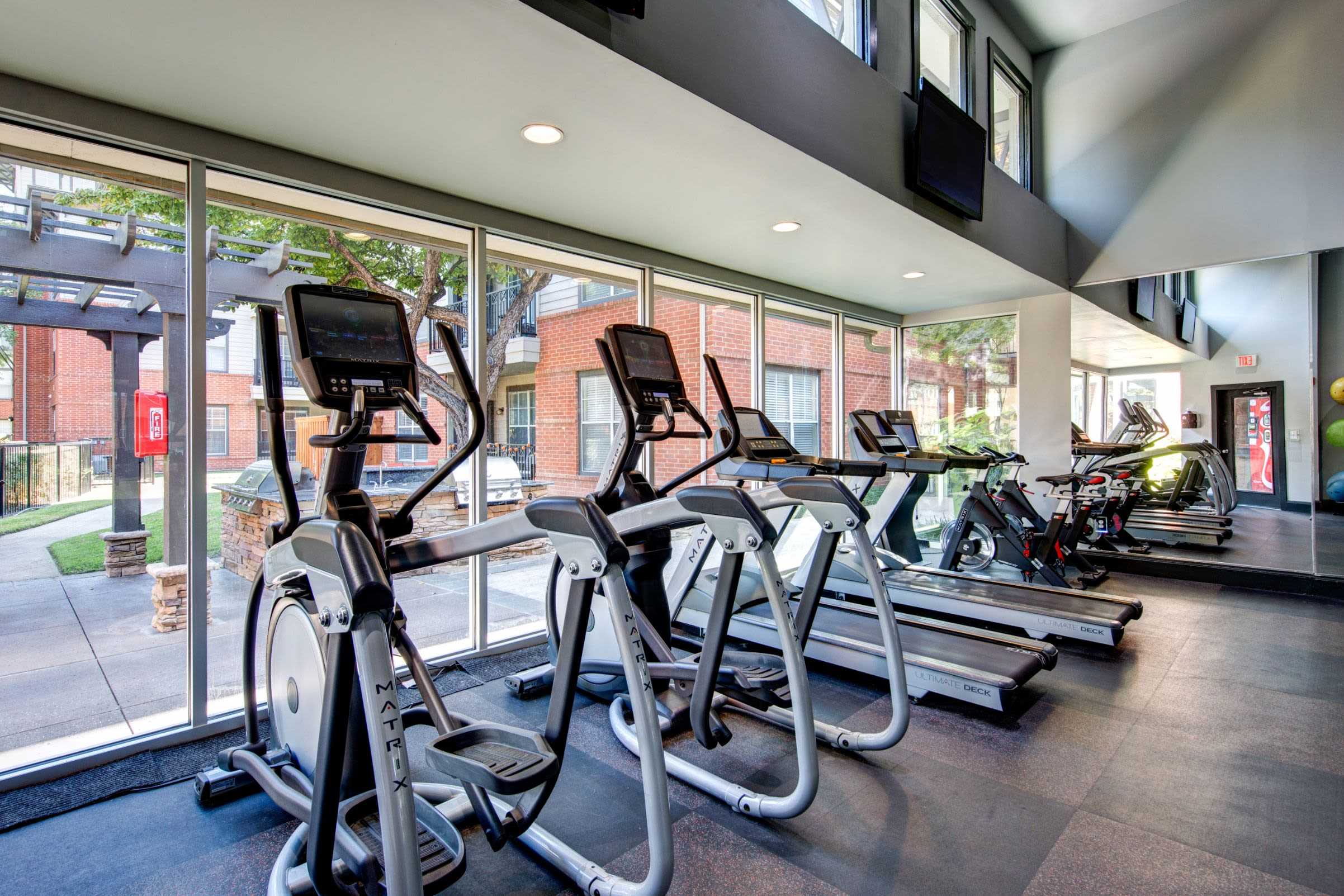 Cardio machines lined up near floor to ceiling windows at Marquis on Gaston in Dallas, Texas