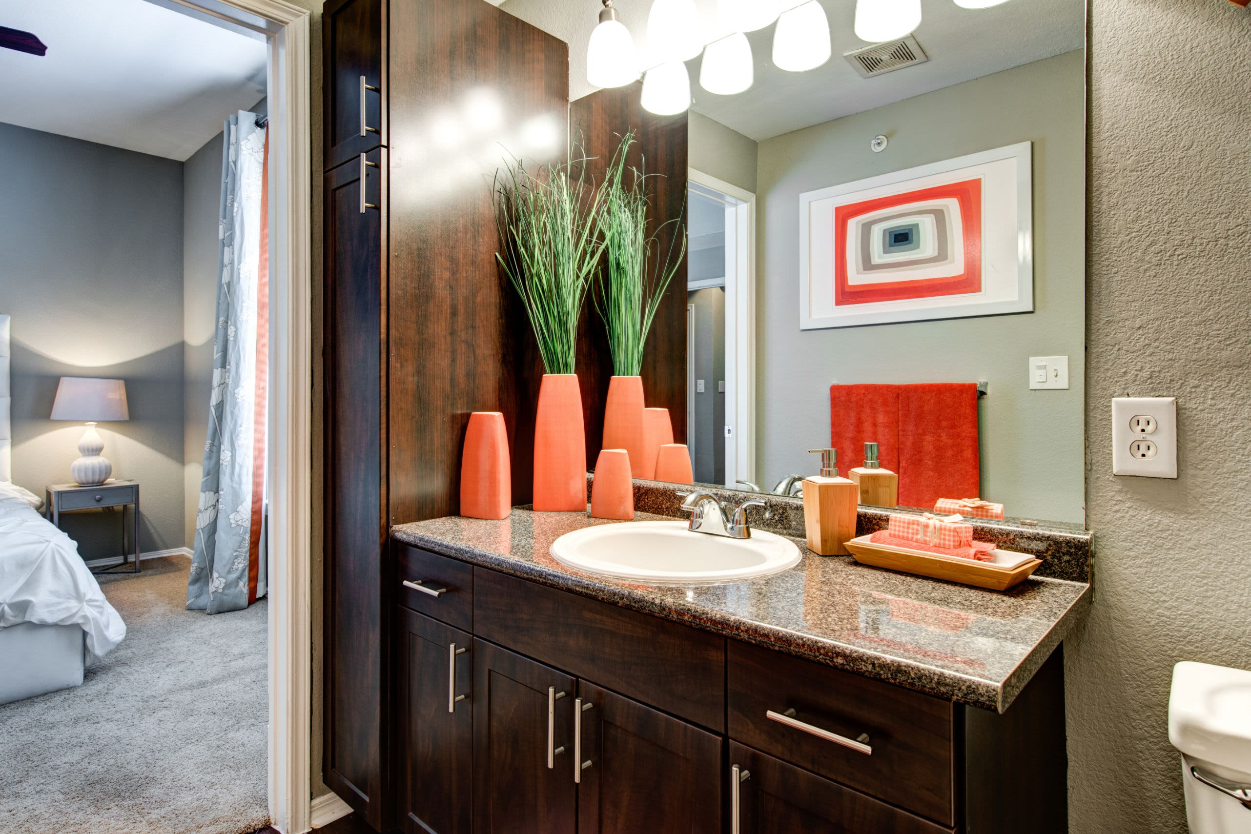 Bathroom with a large mirror and dark brown cabinets at Marquis on Gaston in Dallas, Texas