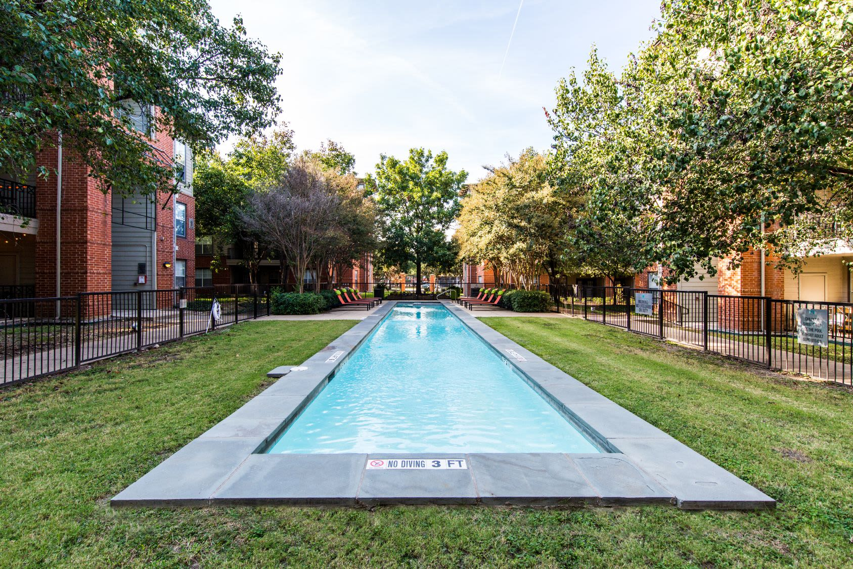 Long and skinny swimming pool surrounded by grass at Marquis on Gaston in Dallas, Texas