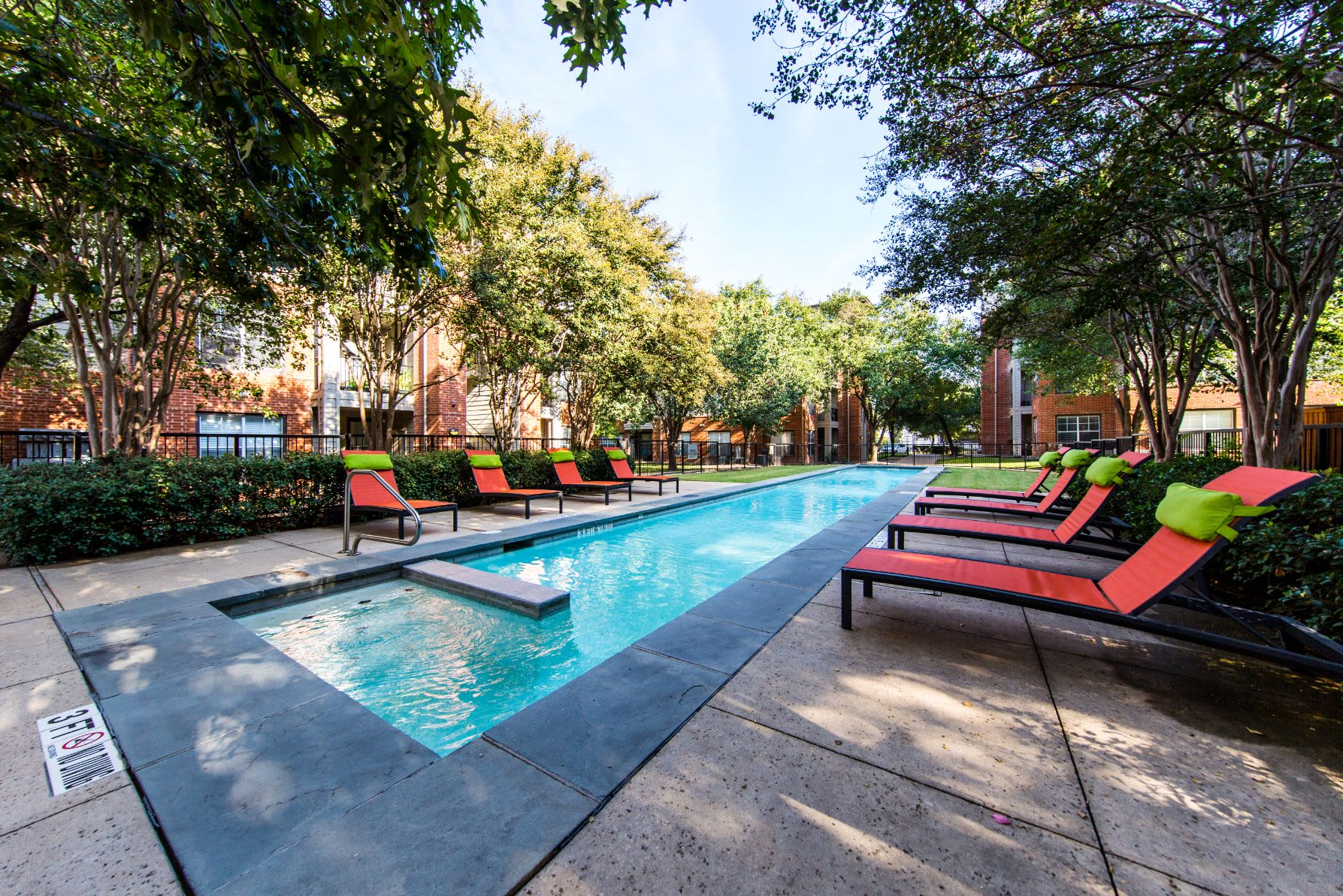 Long and slender swimming pool with lounge chairs on deck at Marquis on Gaston in Dallas, Texas