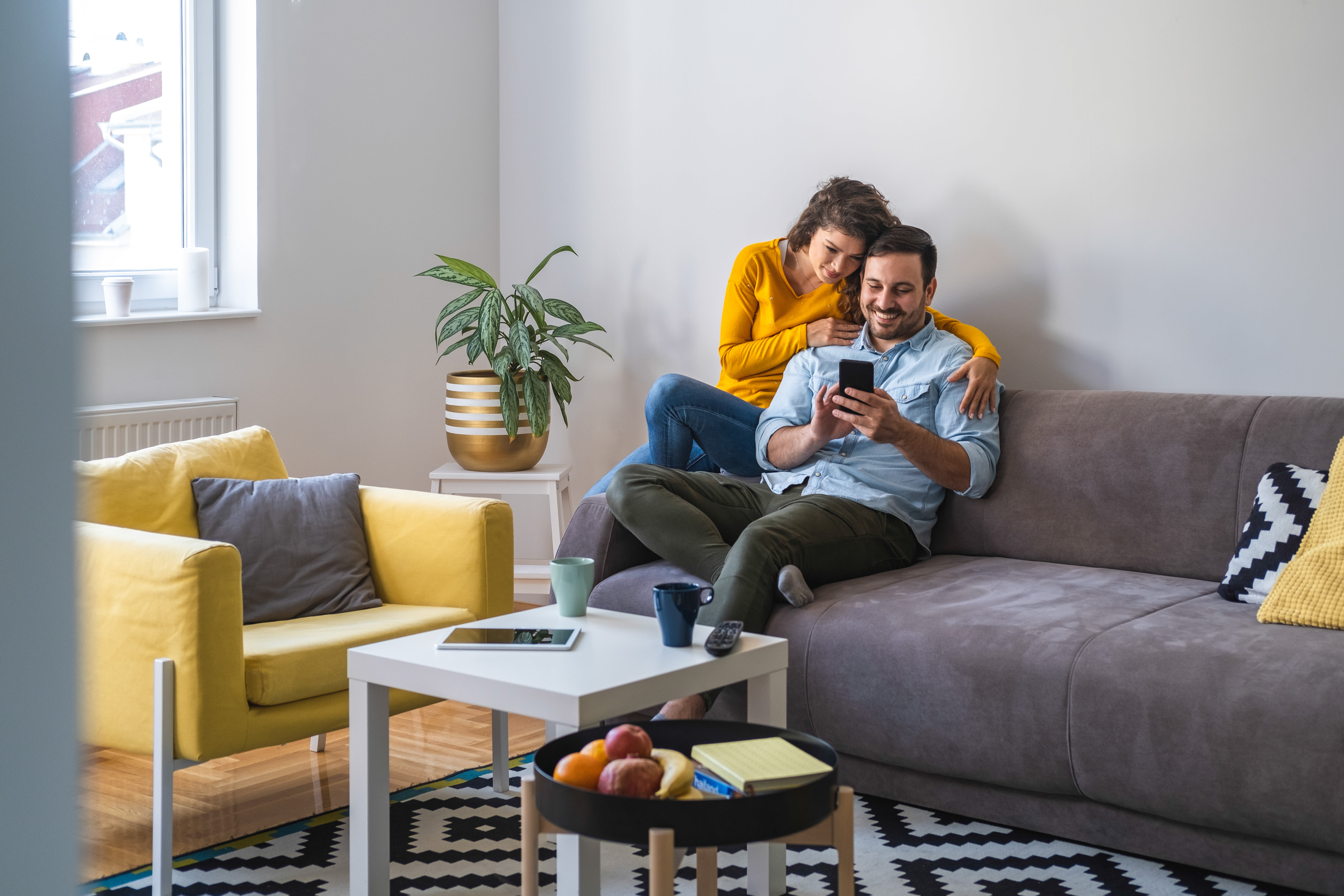 Couple relaxing together in the living room at The Residences at Sawmill Station in Morton Grove, Illinois