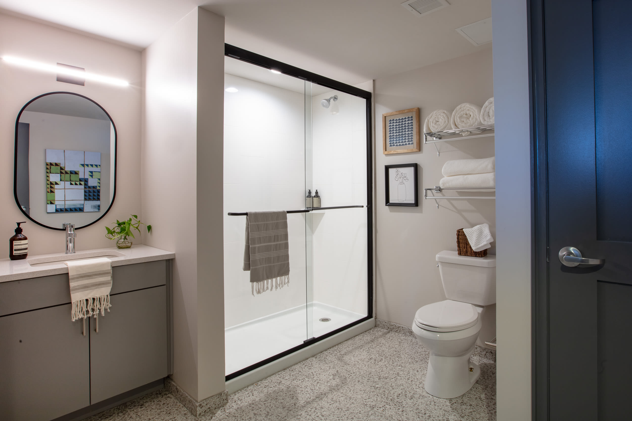 Glass shower doors and tiled flooring in a model home's bathroom at Thirteen15 in New Orleans, Louisiana