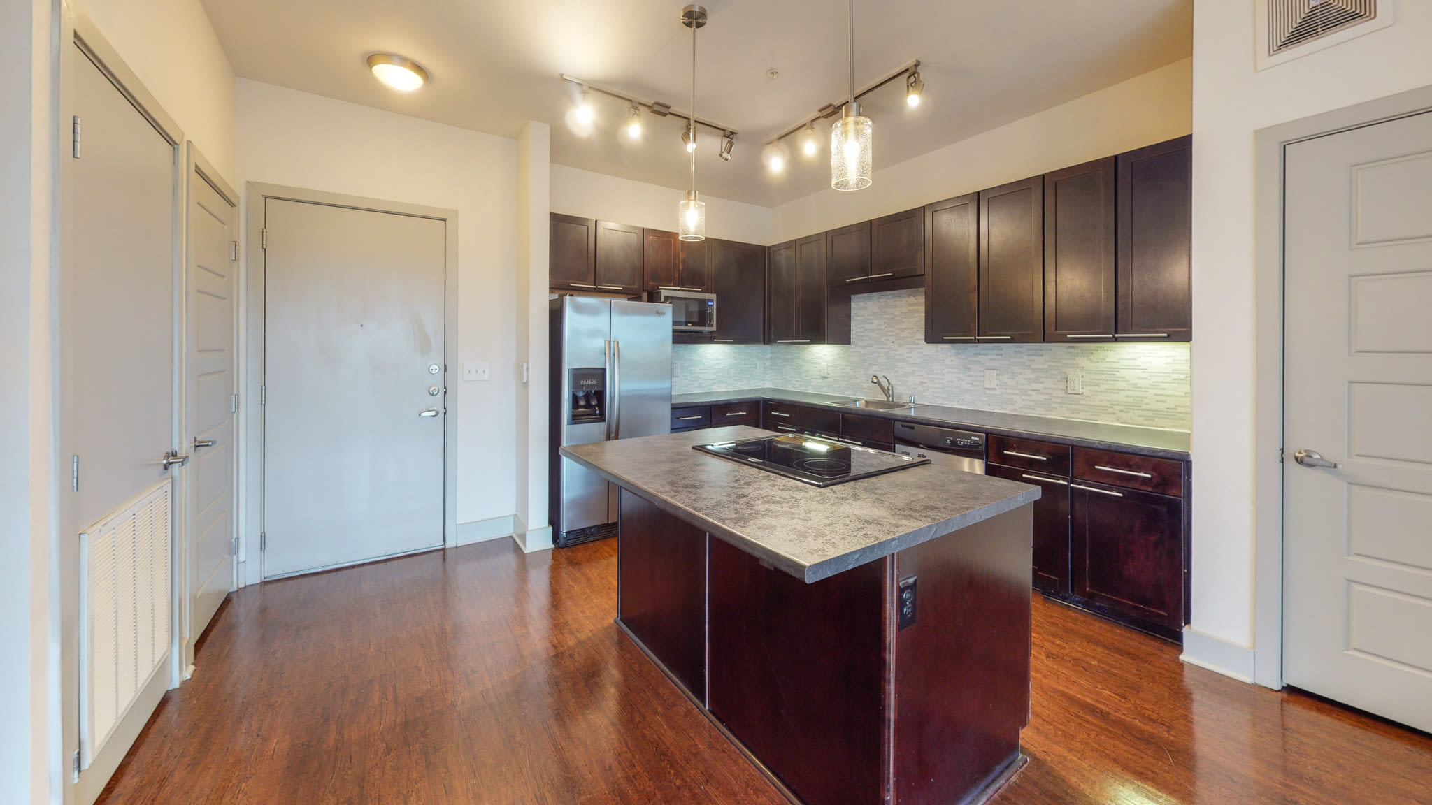 steel appliance kitchen with wood floors and bar seating island at Bellrock Bishop Arts in Dallas, Texas
