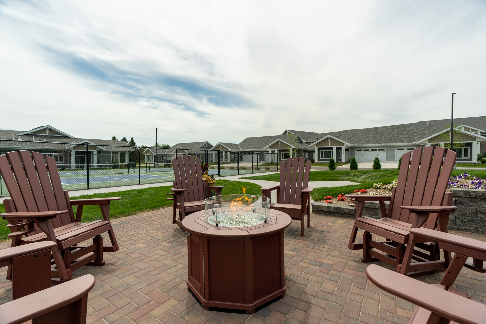 Community fire pit and outdoor lounger area at The Fields at Arbor Glen in Lake Elmo, Minnesota