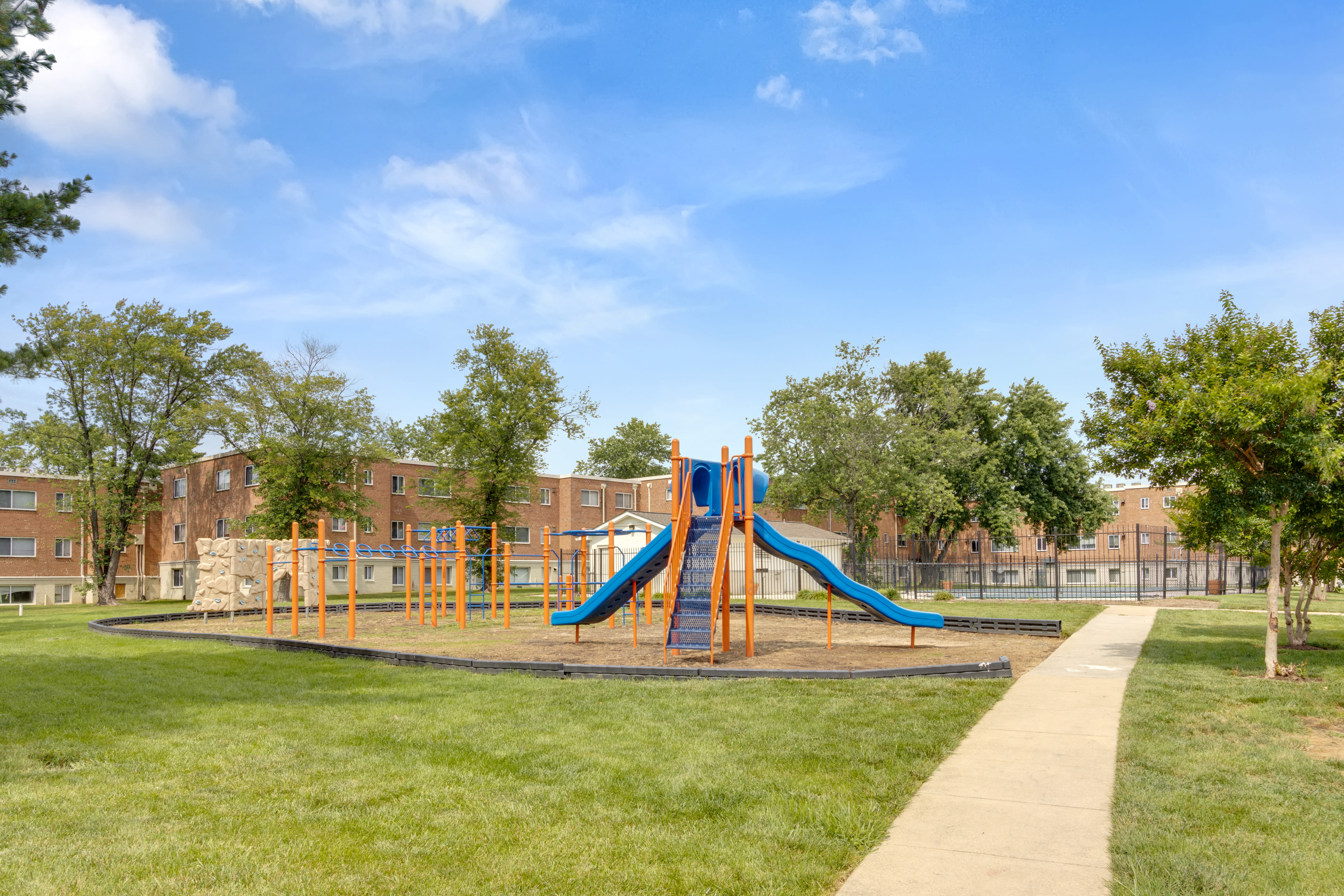 Playground, walking path, and grass field at Regency Pointe in Forestville, Maryland