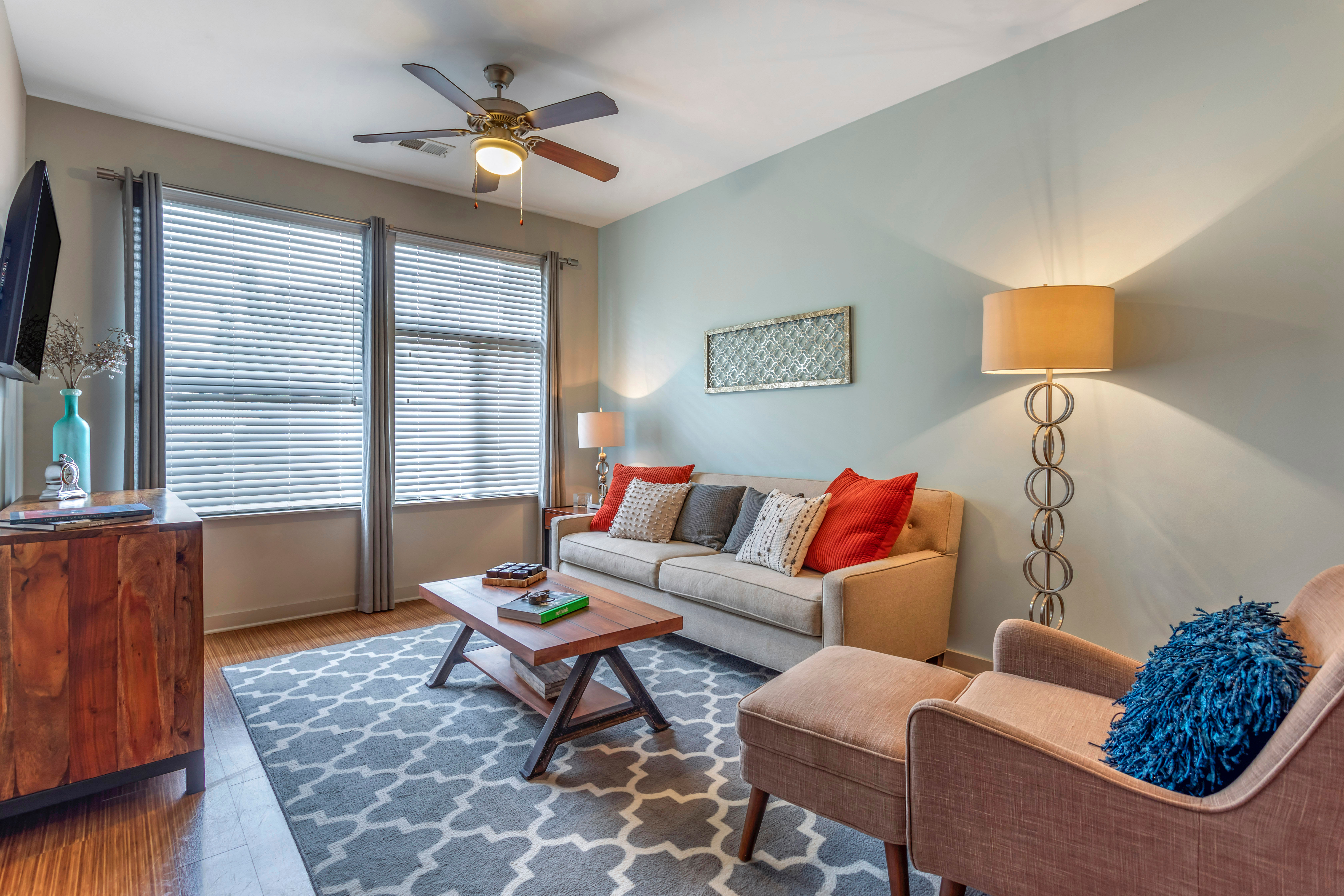 Large open-concept living space with comfortable furnishings in a model home at Olympus Midtown in Nashville, Tennessee