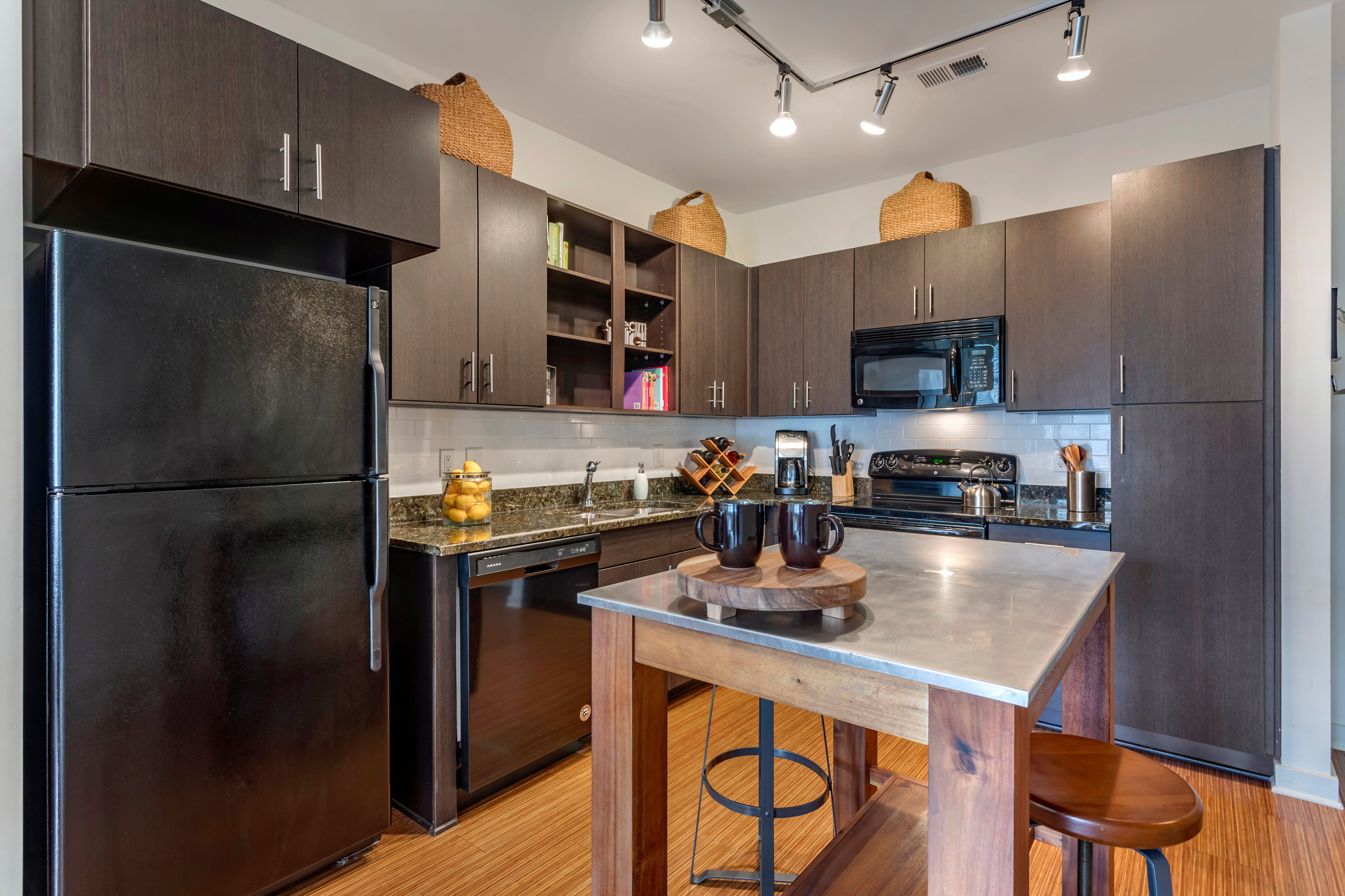 Model home's gourmet kitchen with an island and granite countertops at Olympus Midtown in Nashville, Tennessee