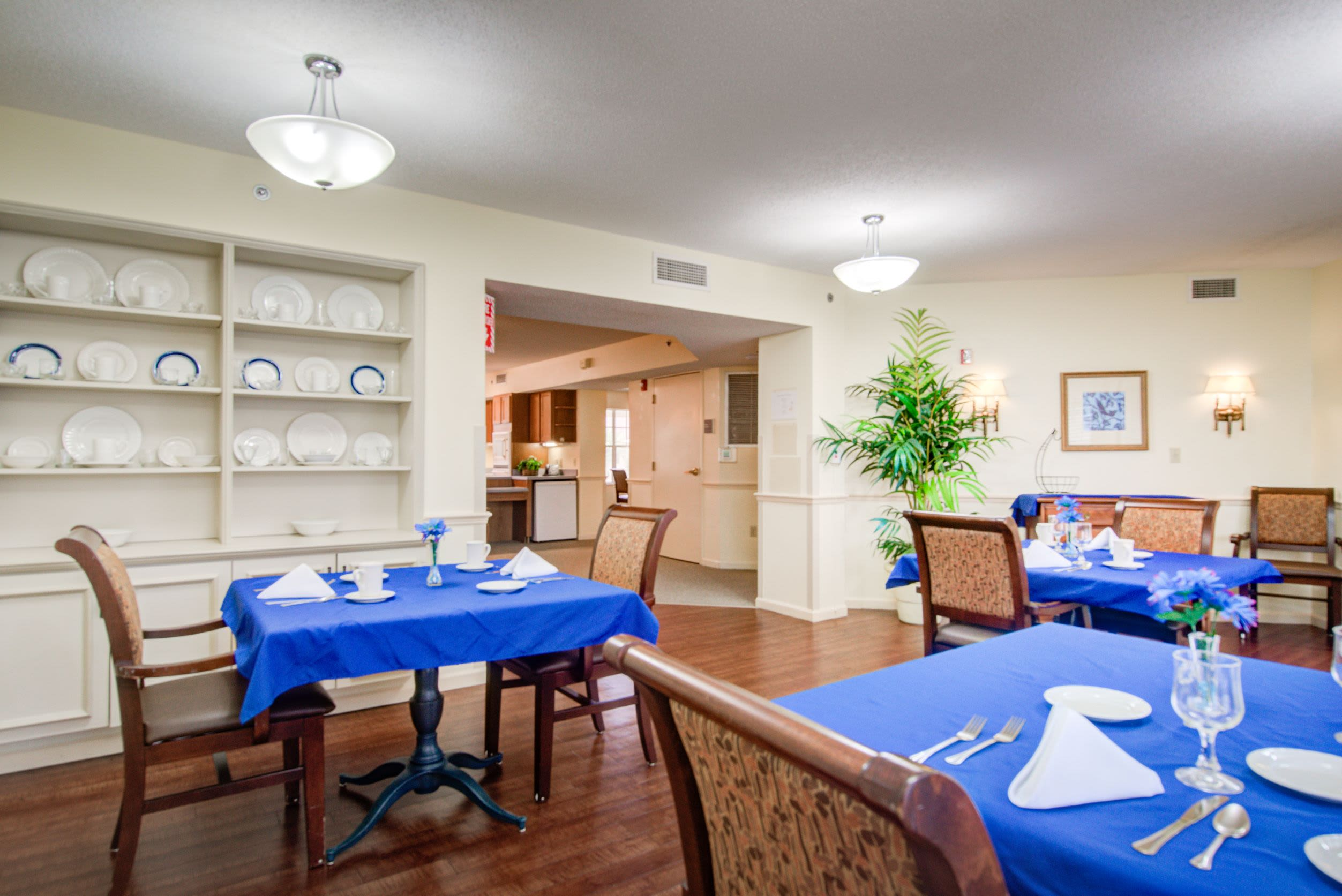 Dining tables with place settings at Truewood by Merrill, Charlotte Center in Port Charlotte, Florida.