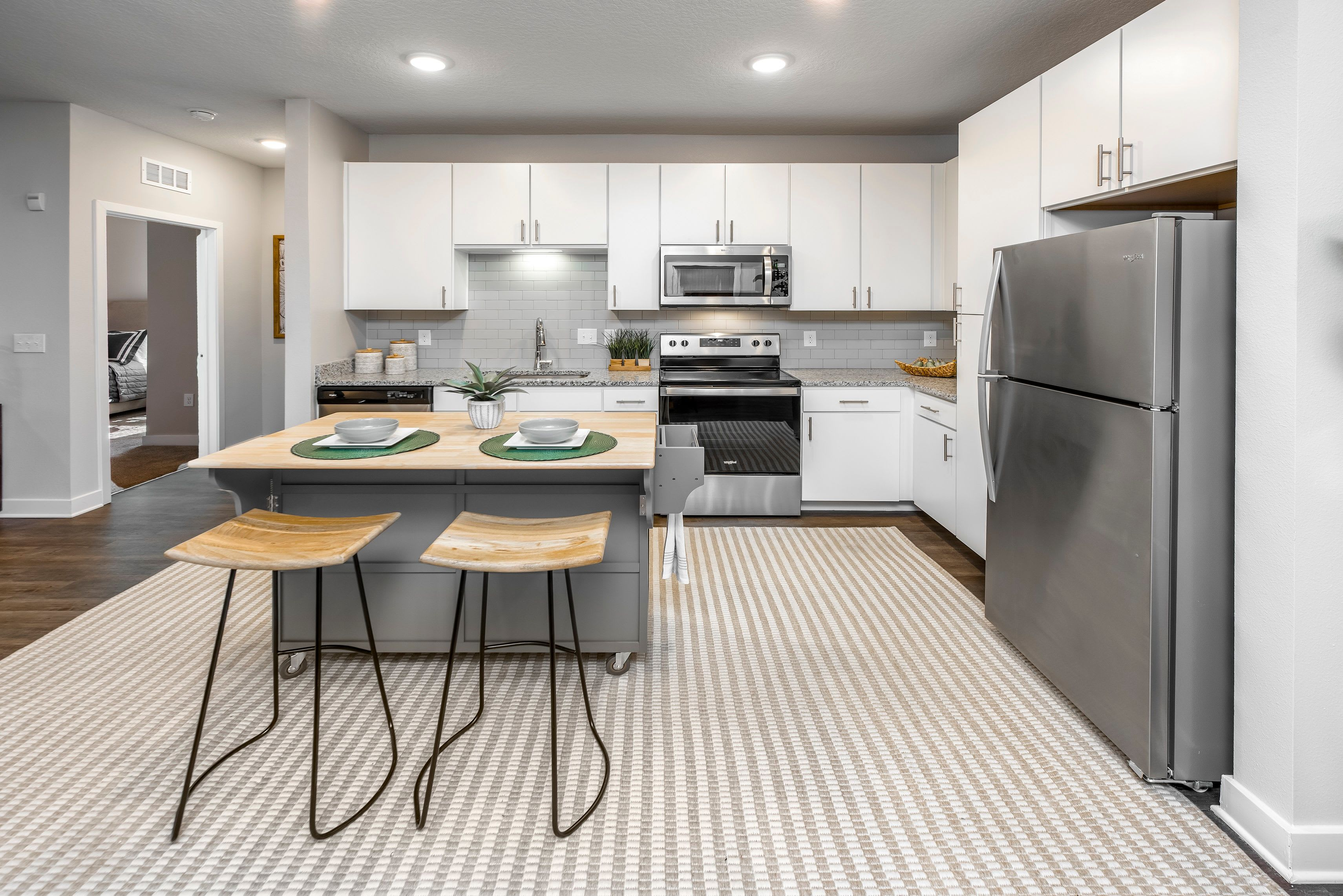 Open concept kitchen with wood floors at Argyle at Oakleaf Town Center in Jacksonville, Florida