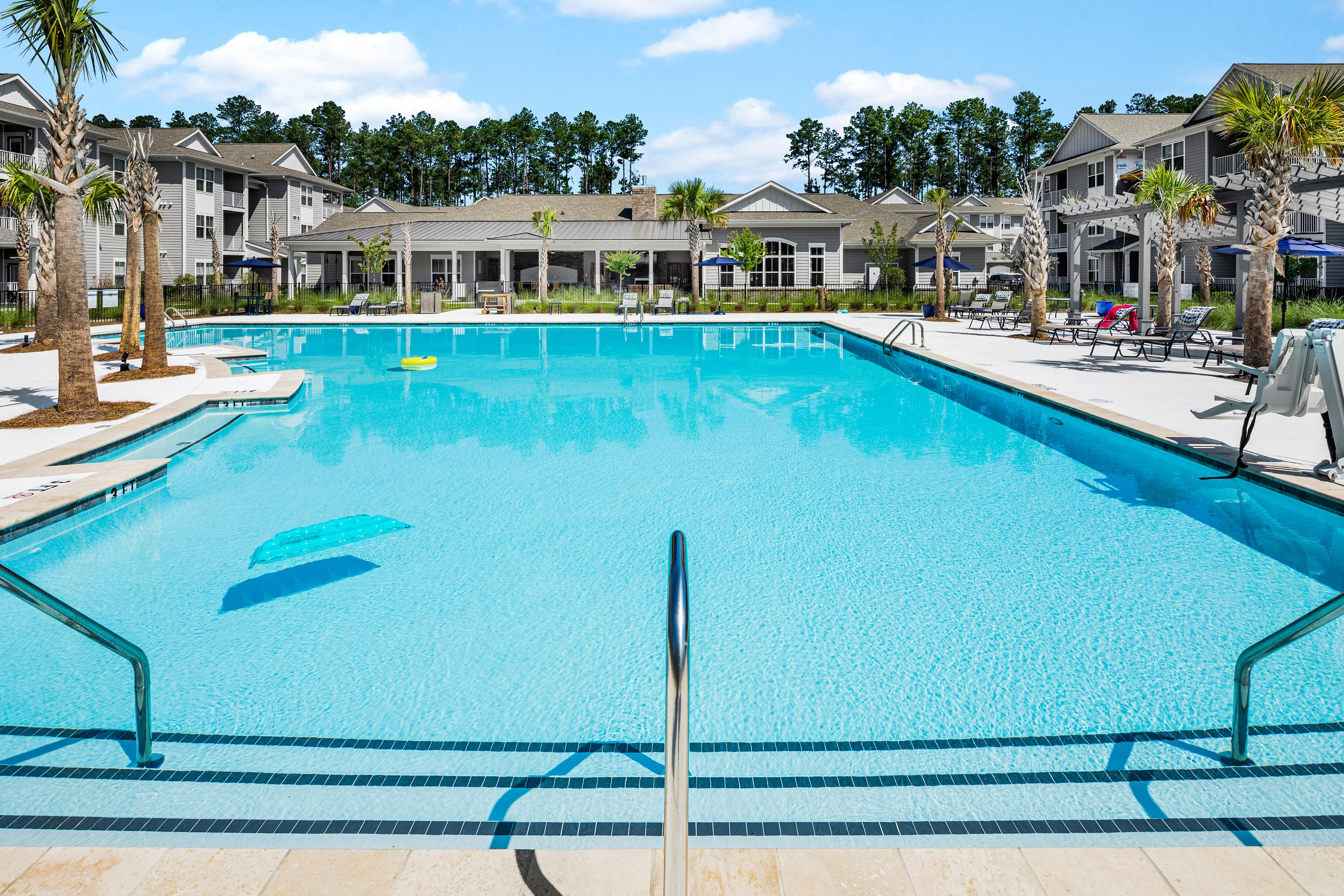 Outdoor grilling area with seating and places to cook poolside at The Isaac in Summerville, South Carolina