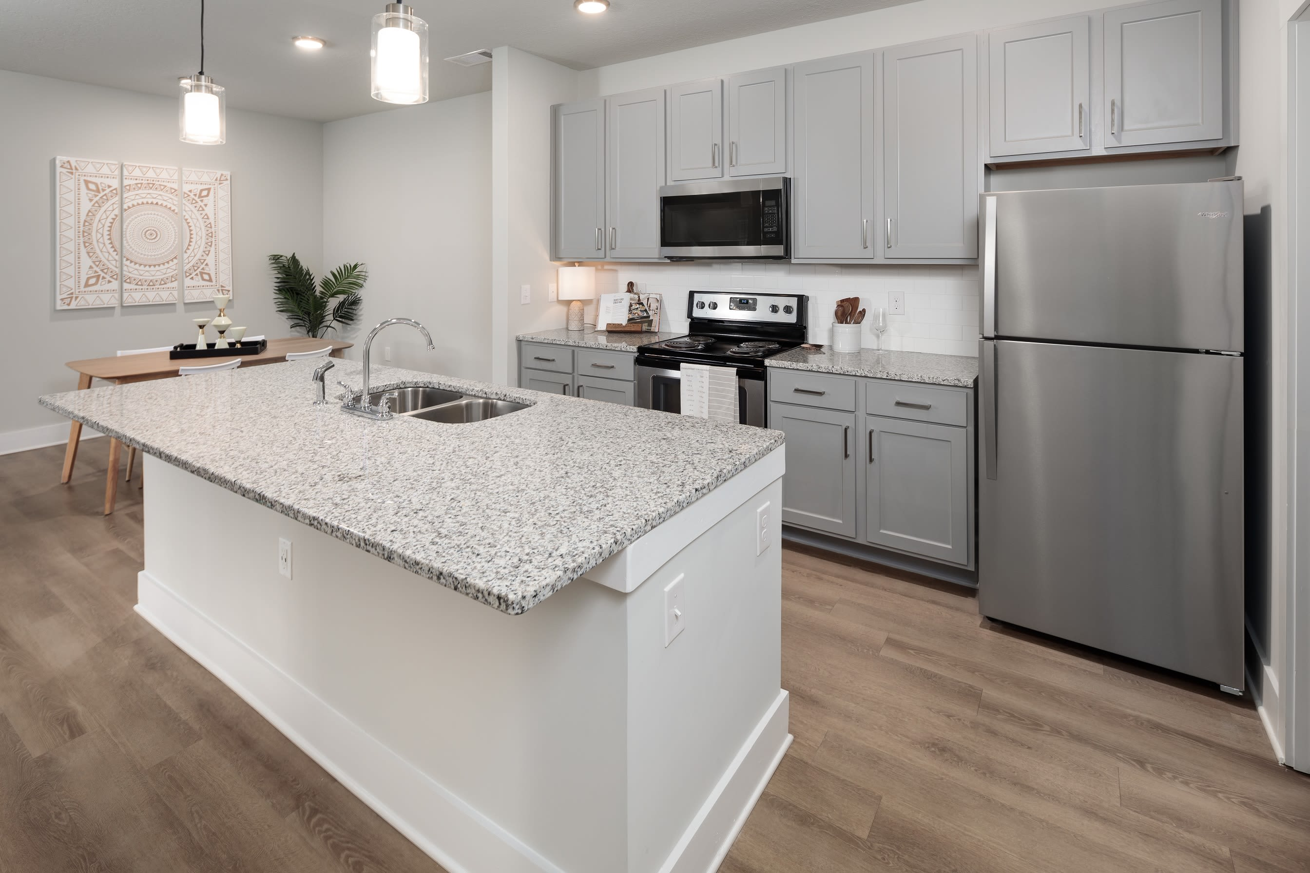 Large kitchen with white cabinets appliances and washer dryer at The Mason in Ladson, South Carolina