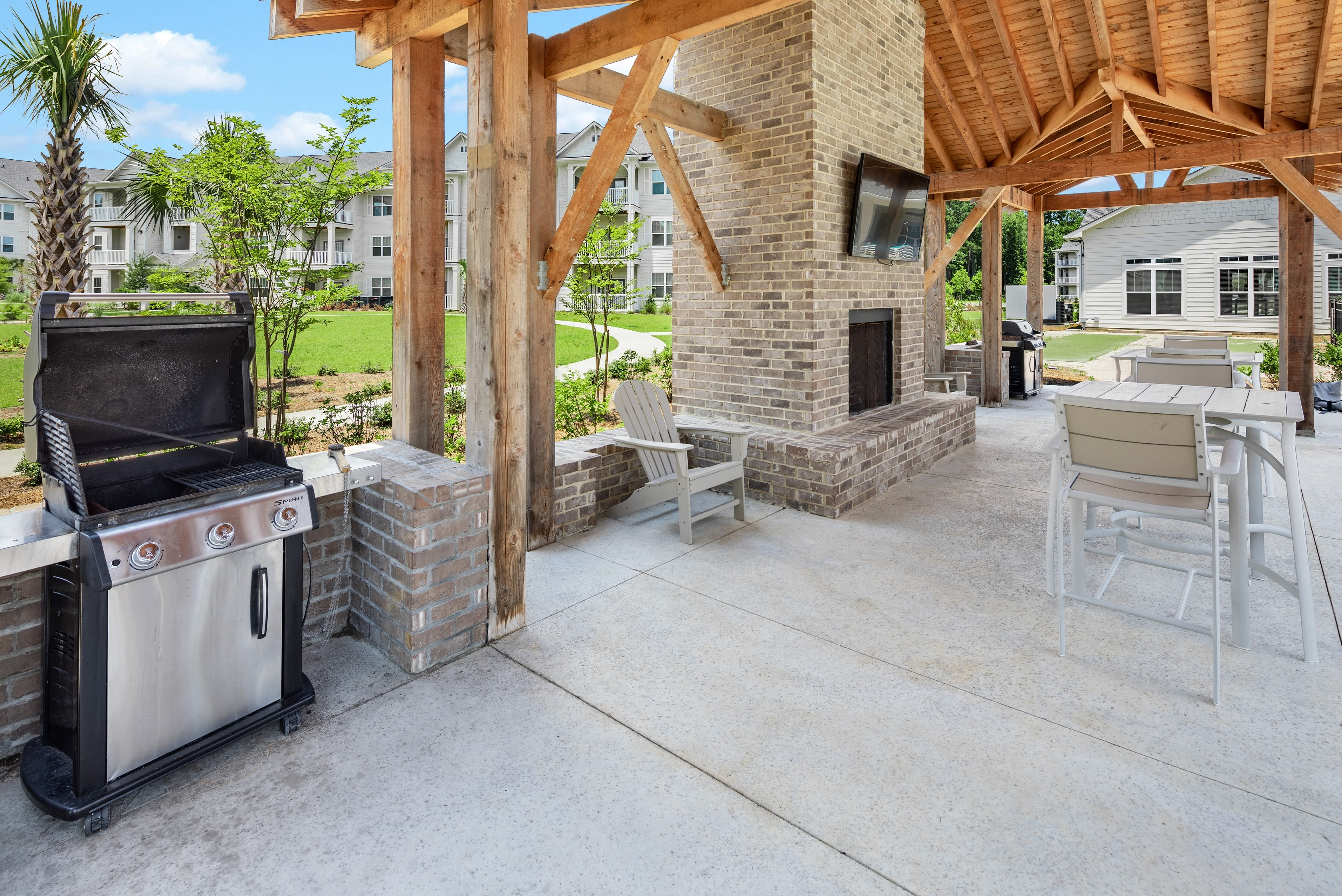 Outdoor grilling area with seating and places to cook poolside at The Mason in Ladson, South Carolina