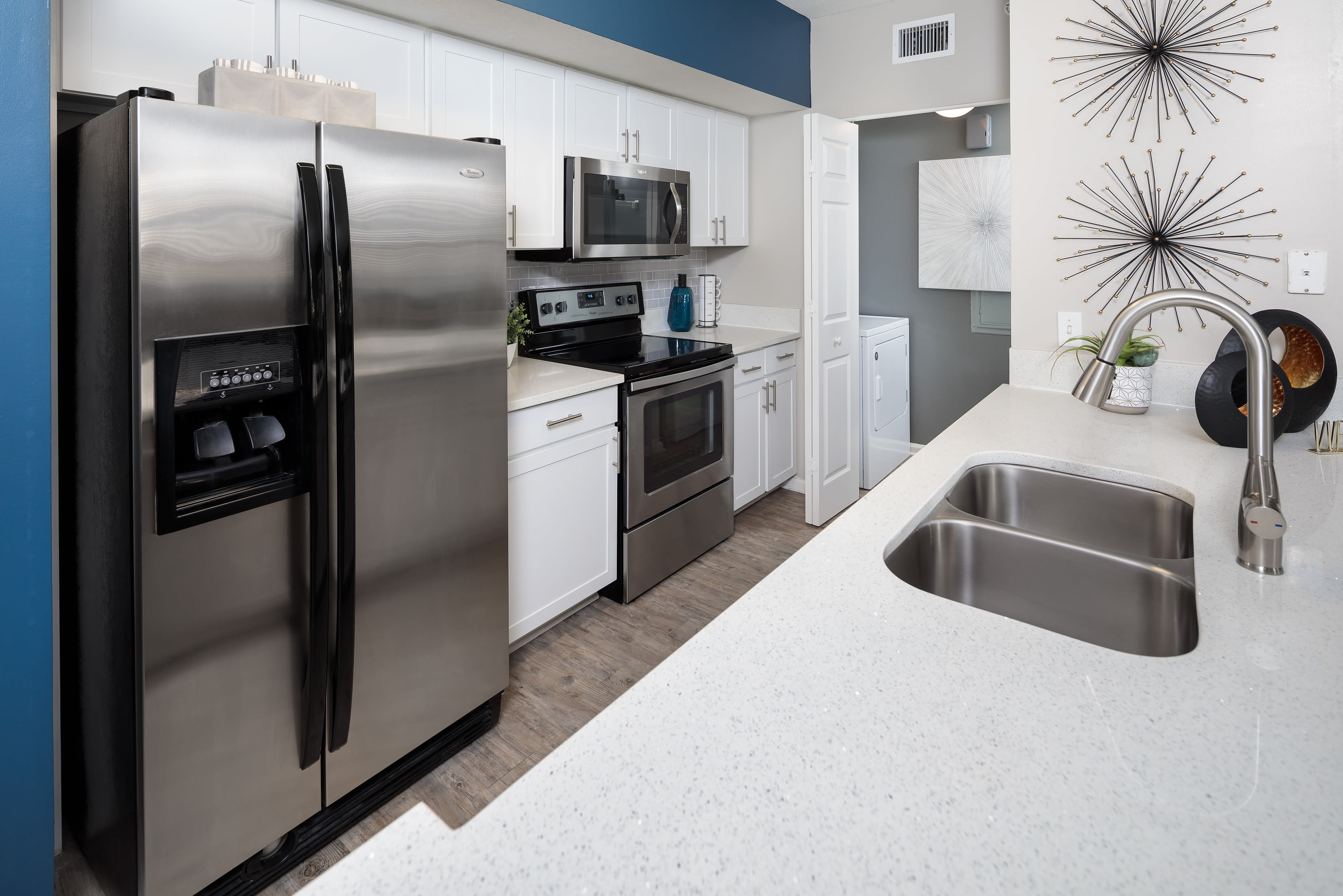 Sleek white cabinets and stainless steel appliances in the kitchen at The Pearl in Ft Lauderdale, Florida