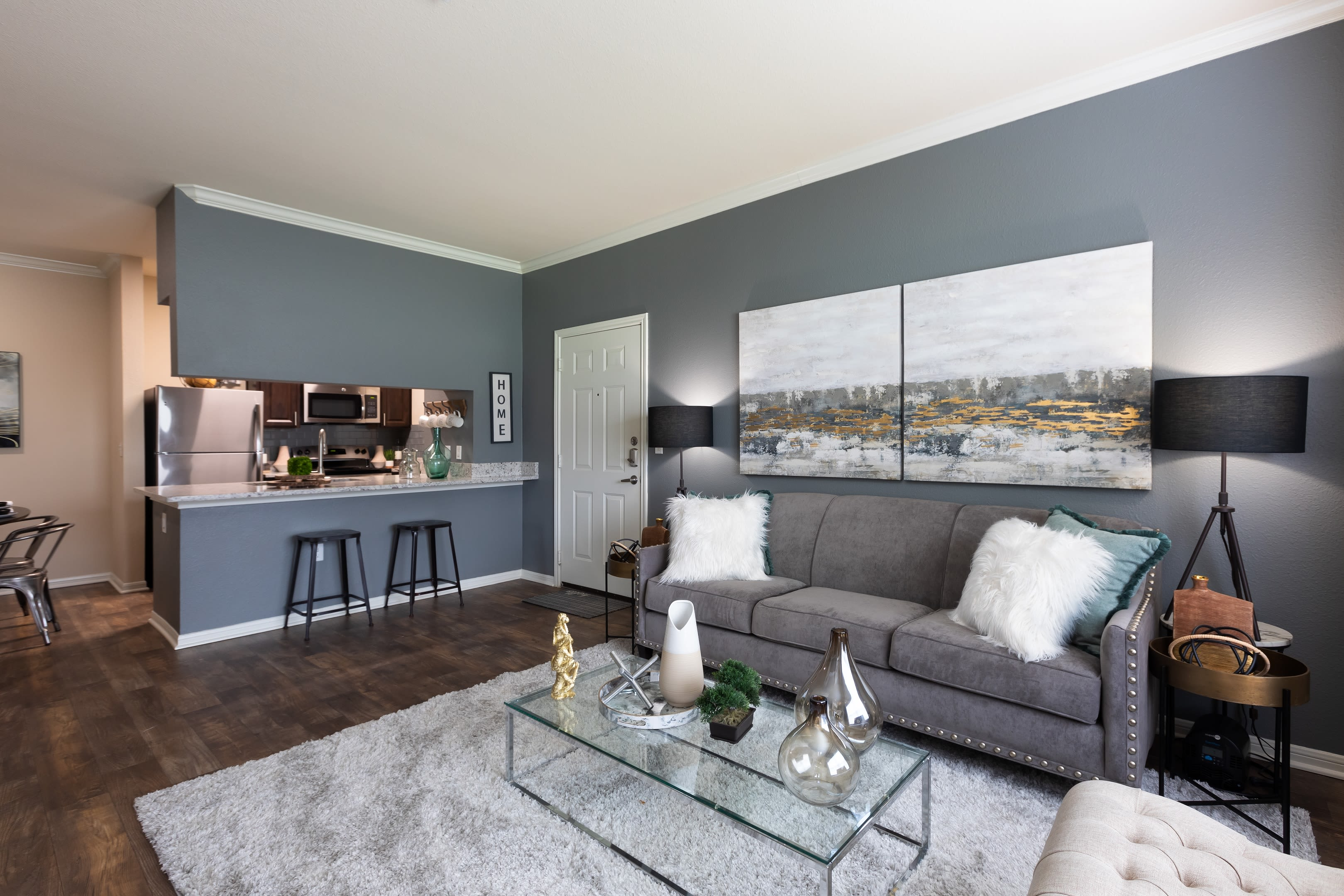 Open-concept floor plan with hardwood floors and accent wall in the living area of model home at Ranch at Hudson Xing in McKinney, Texas