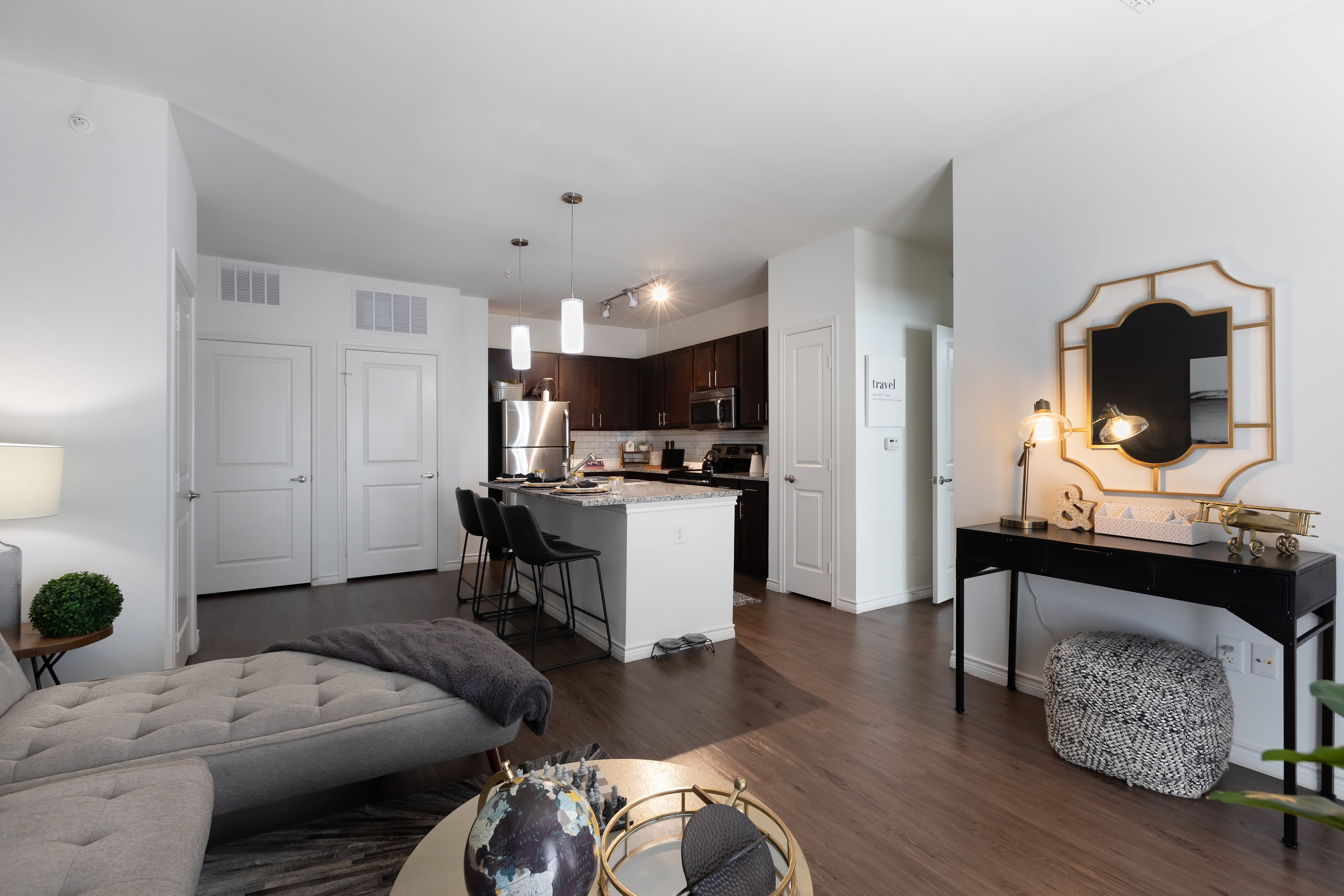 Open-concept layout with hardwood floors in model home at 4 Corners Apartments in Frisco, Texas