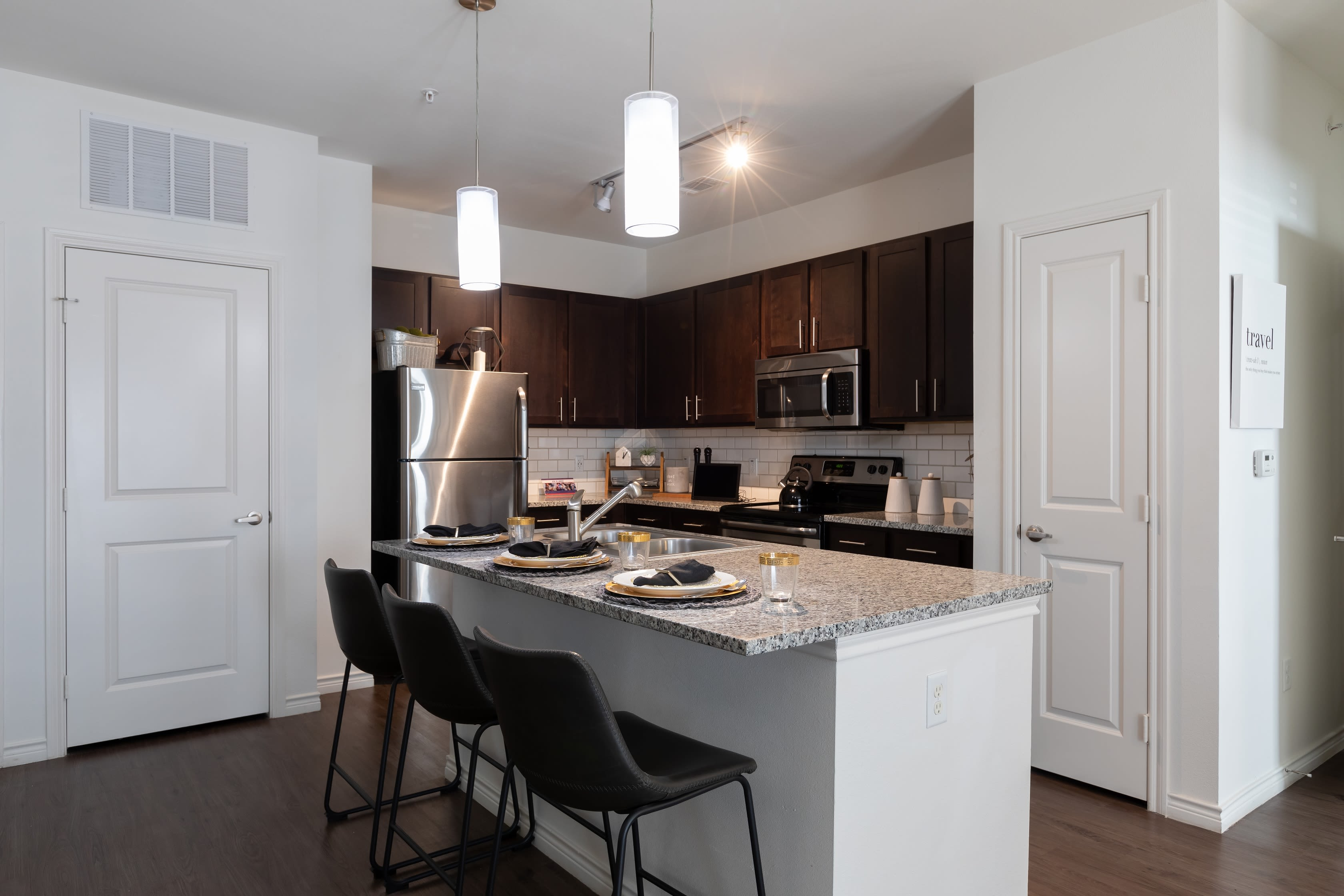 Kitchen island with seating in a model apartment at 4 Corners Apartments in Frisco, Texas
