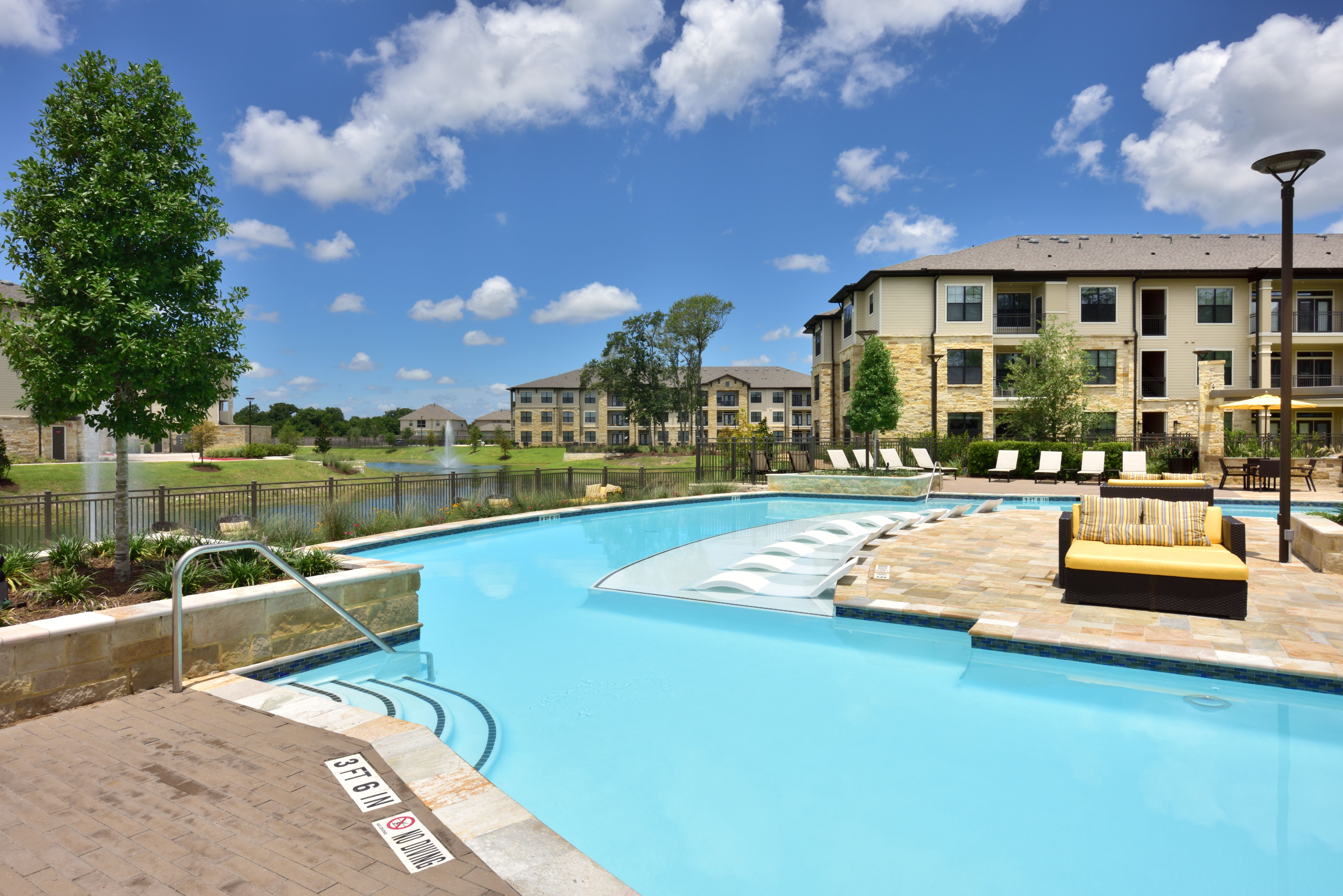 Resort style pool with lounge chairs and tables on pool deck at Olympus Falcon Landing in Katy, TX