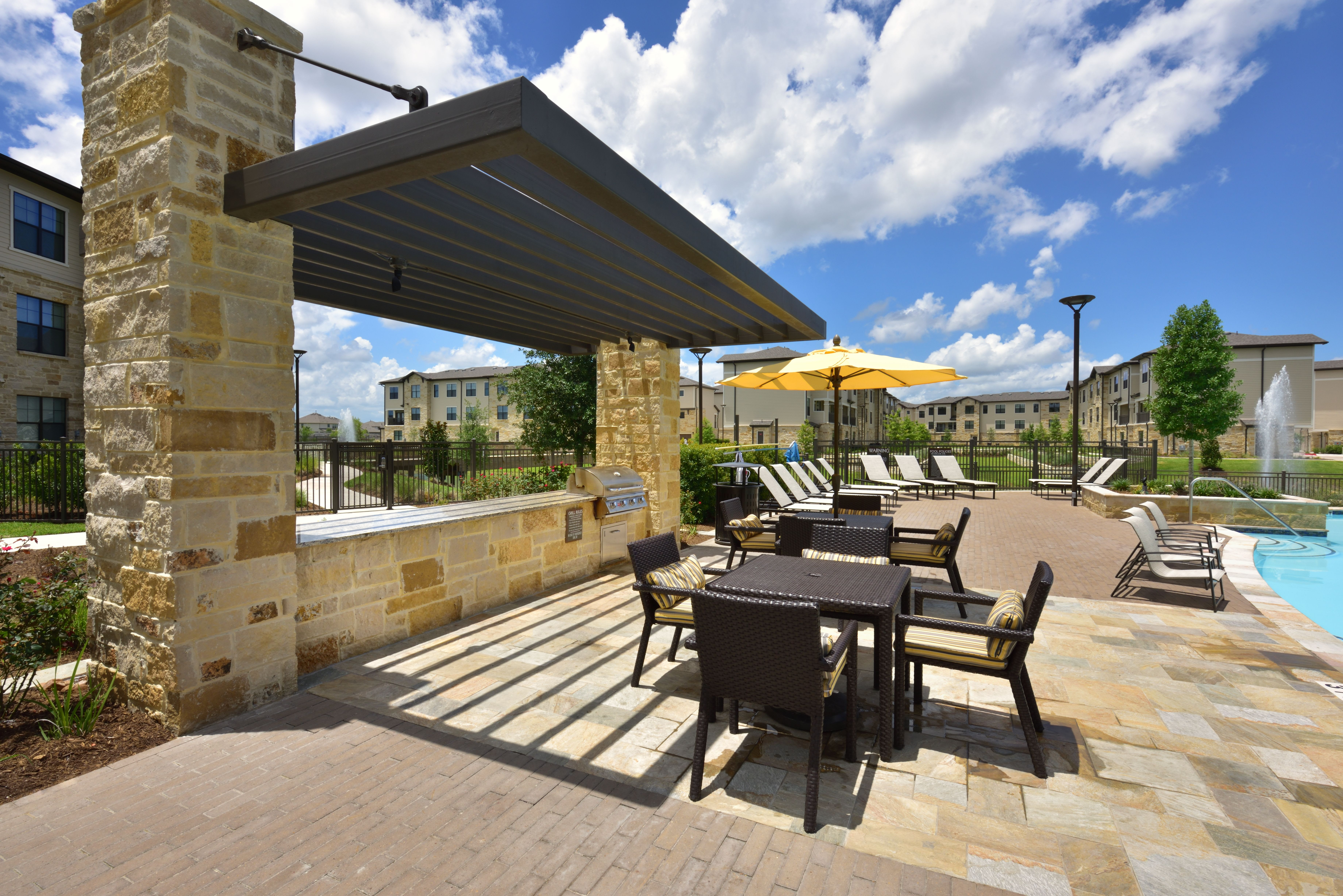 Stone BBQ with sitting tables and chairs on pool deck at Olympus Falcon Landing in Katy, TX
