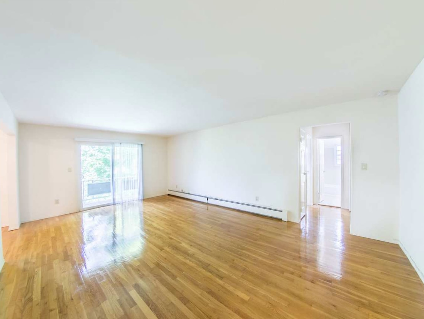 Large living room with wood flooring at The Manors in Pomona, New York