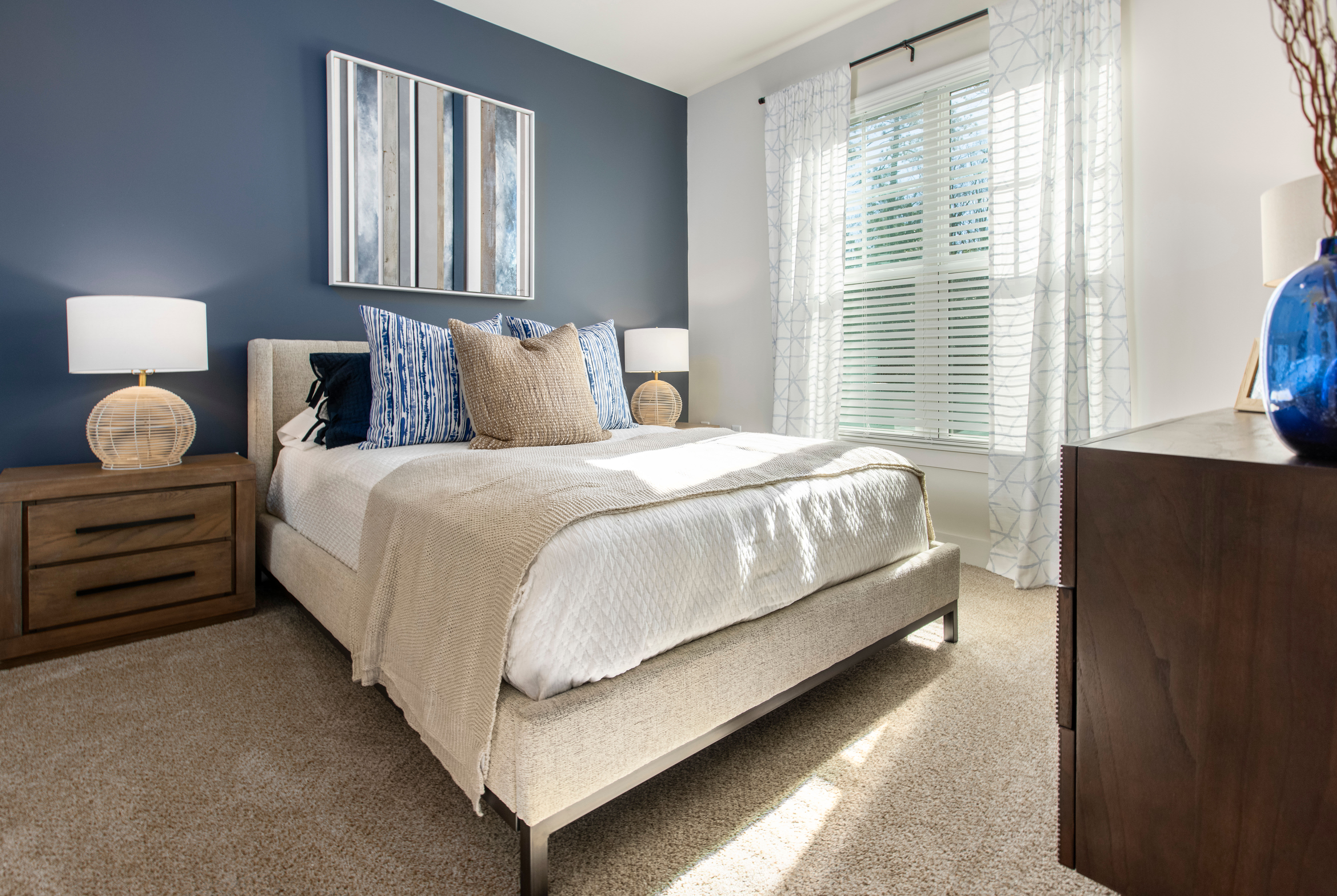 Brightly lit model bedroom at South City Apartments in Summerville, South Carolina